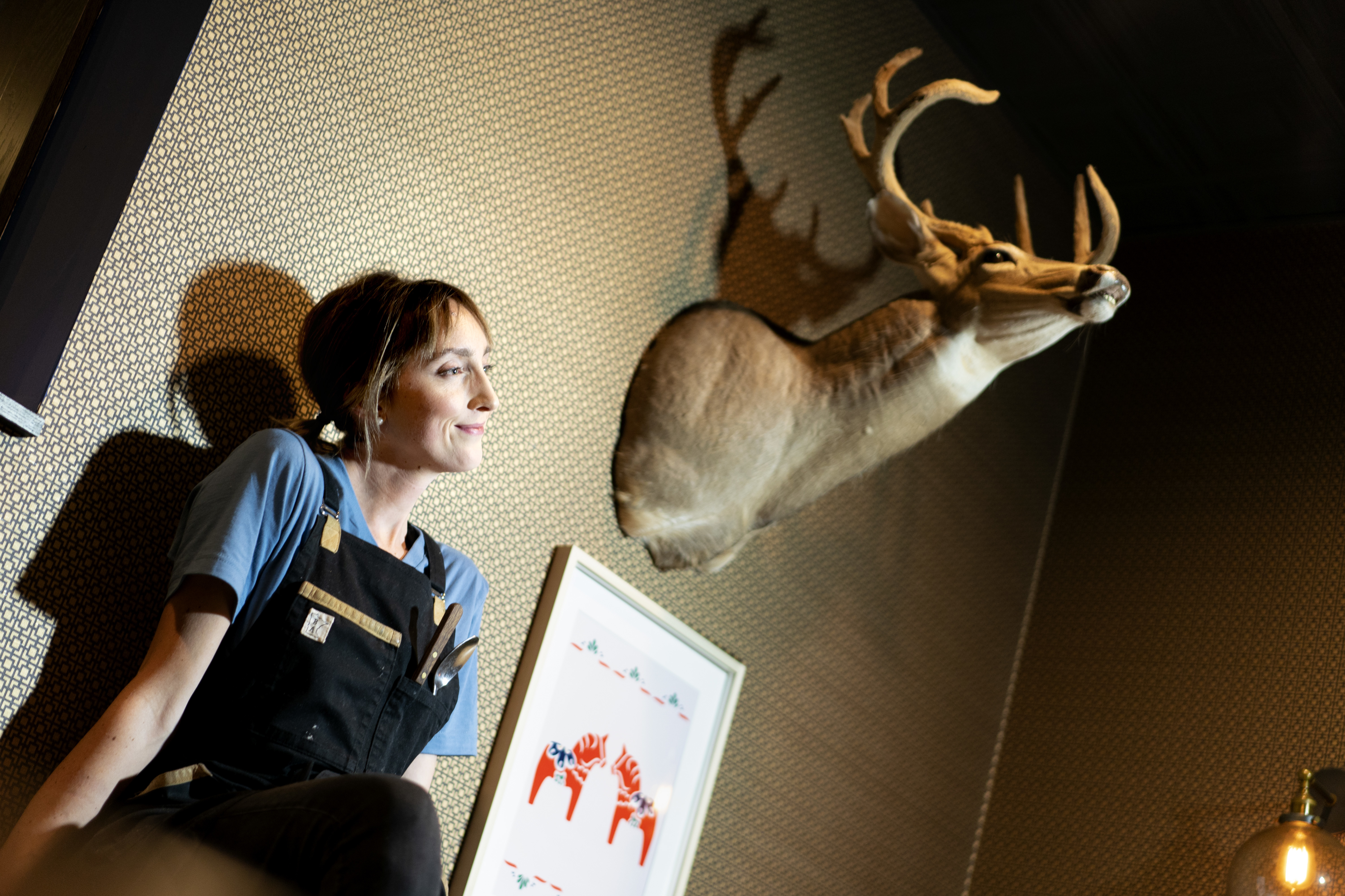 Karyn Tomlinson sits under a mounted deer head, looking into the distance