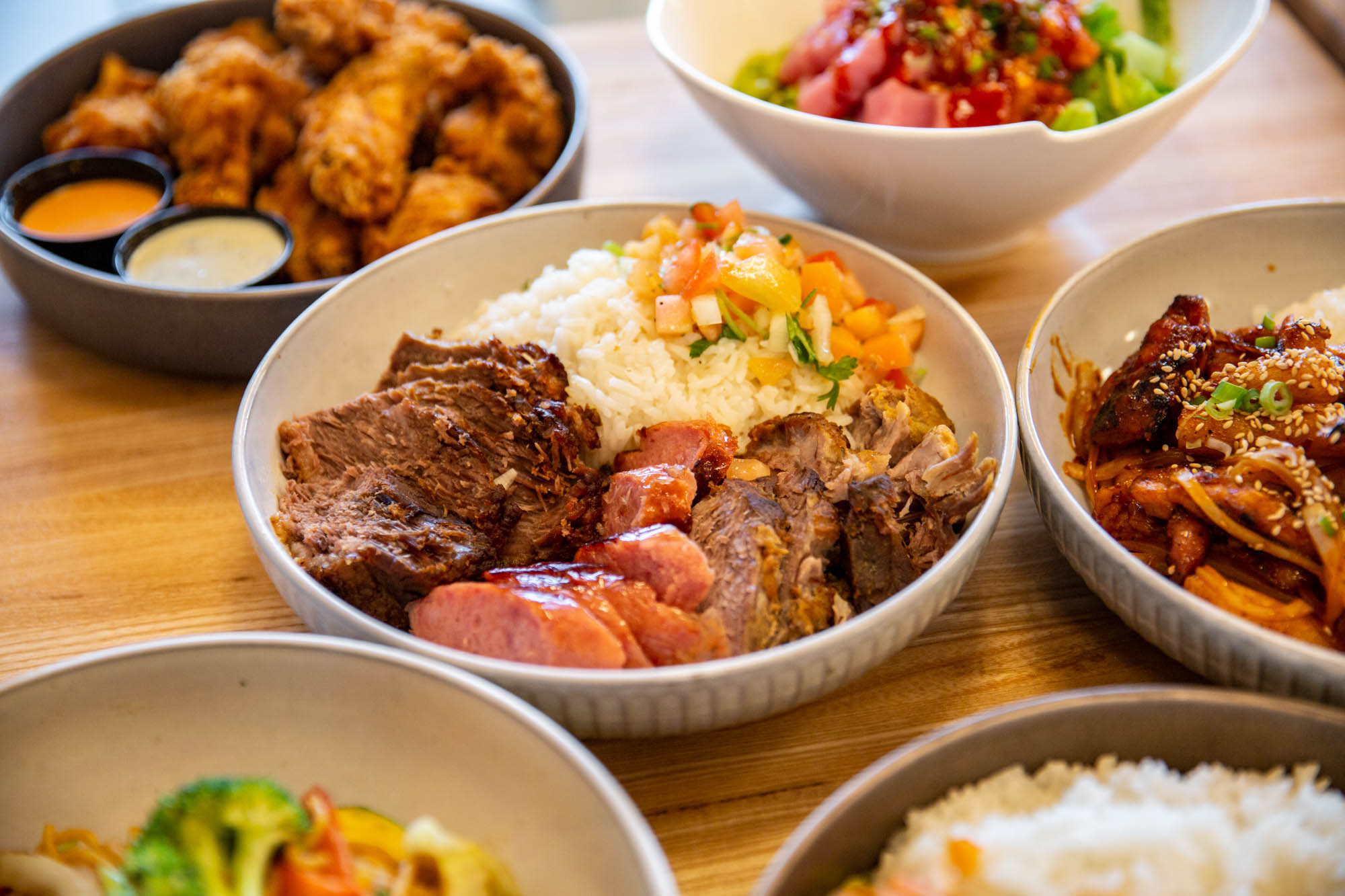 Several dishes from Tá Jóia restaurant, including Korean-style wings and a brisket, slow-cooked pork, and sausage medley with Spanish rice.