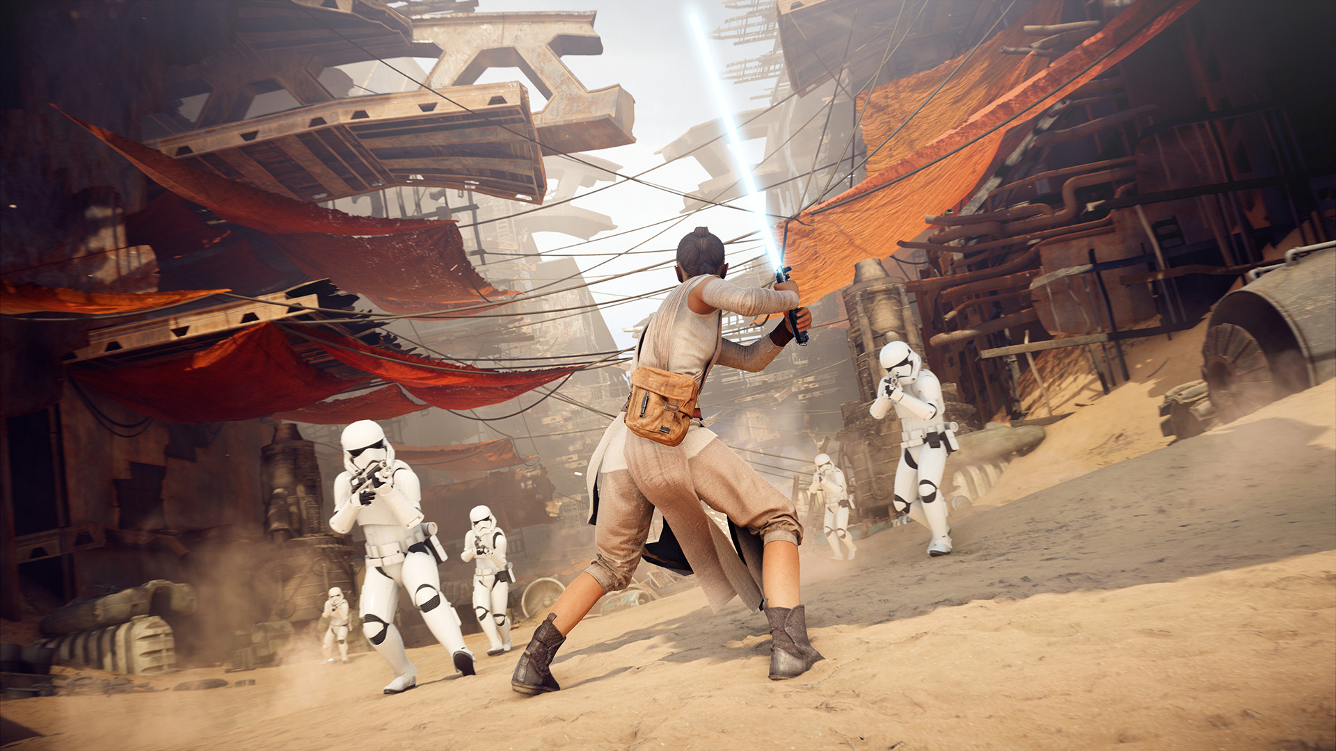 Rey holds her lightsaber in a defensive position as Stormtroopers run toward her