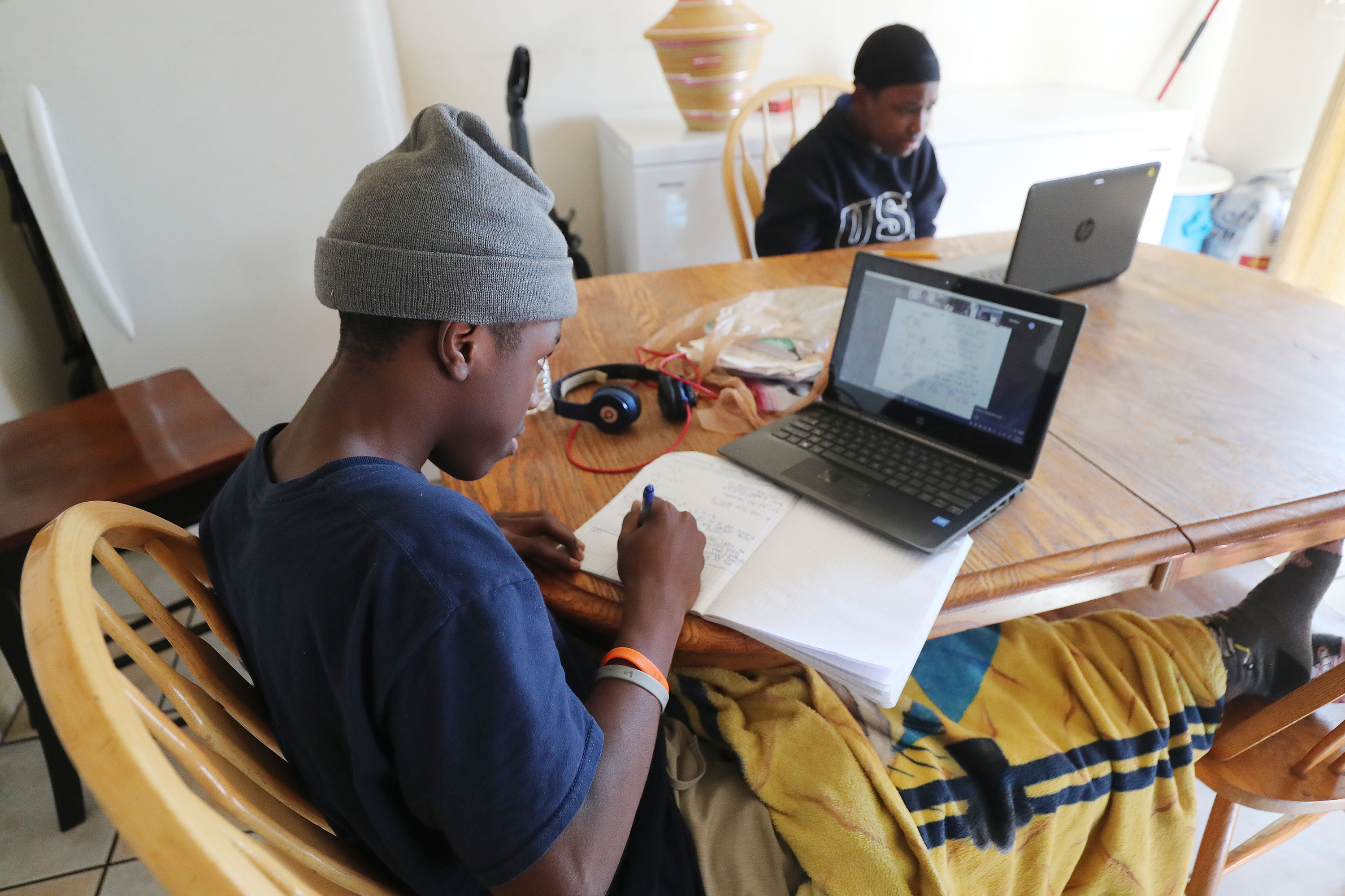 Richard Vyukusengere, left, and his brother, Didace Mahoro, attend school remotely at home in Salt Lake City on Tuesday, Jan. 19, 2021. Salt Lake City parents who are suing the Salt Lake City School District are asking for an injunction to allow for an in-person learning option.
