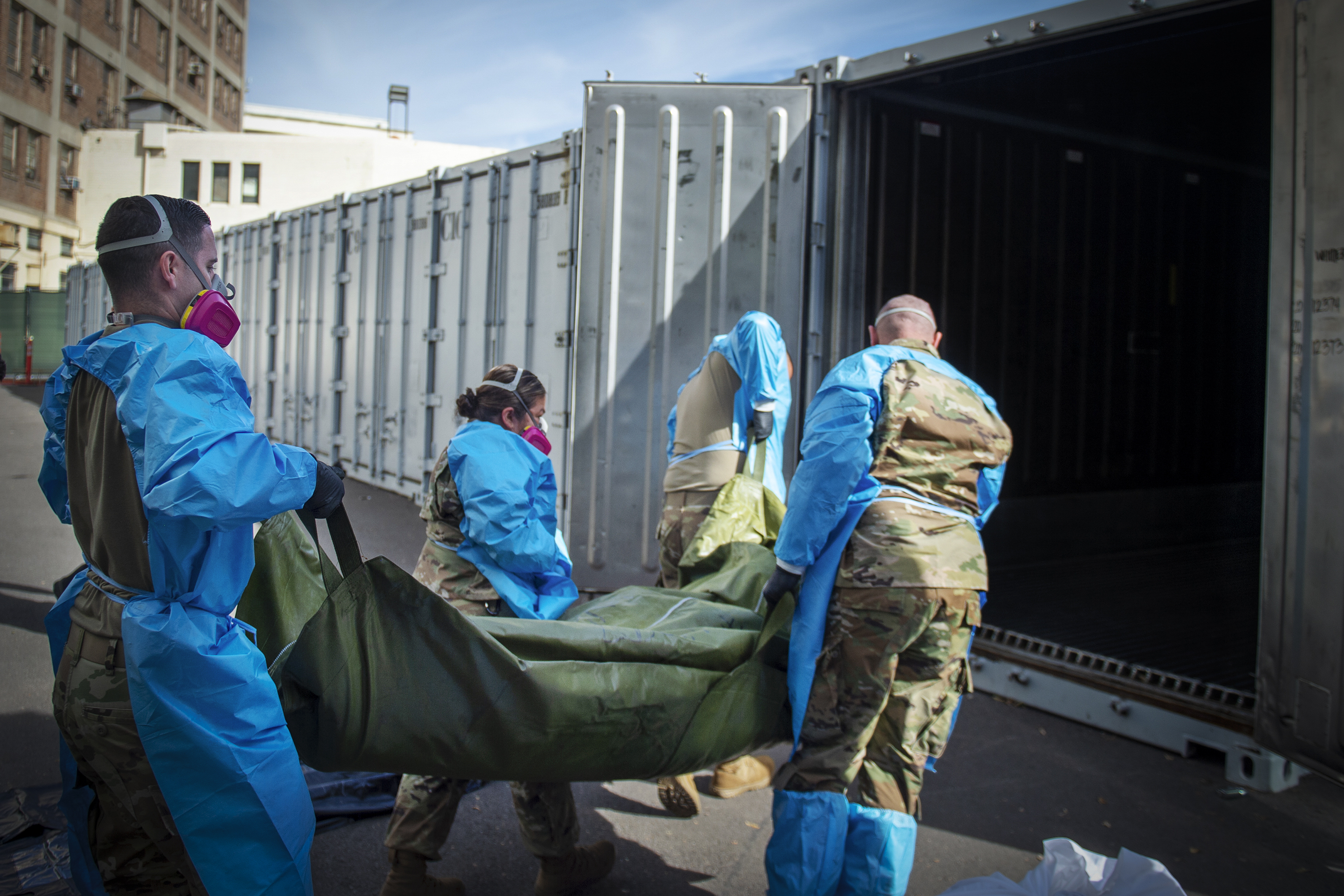 National Guard member wearing camouflage covered in hospital gowns and masks load a dead body in a bag into an outdoor storage container.