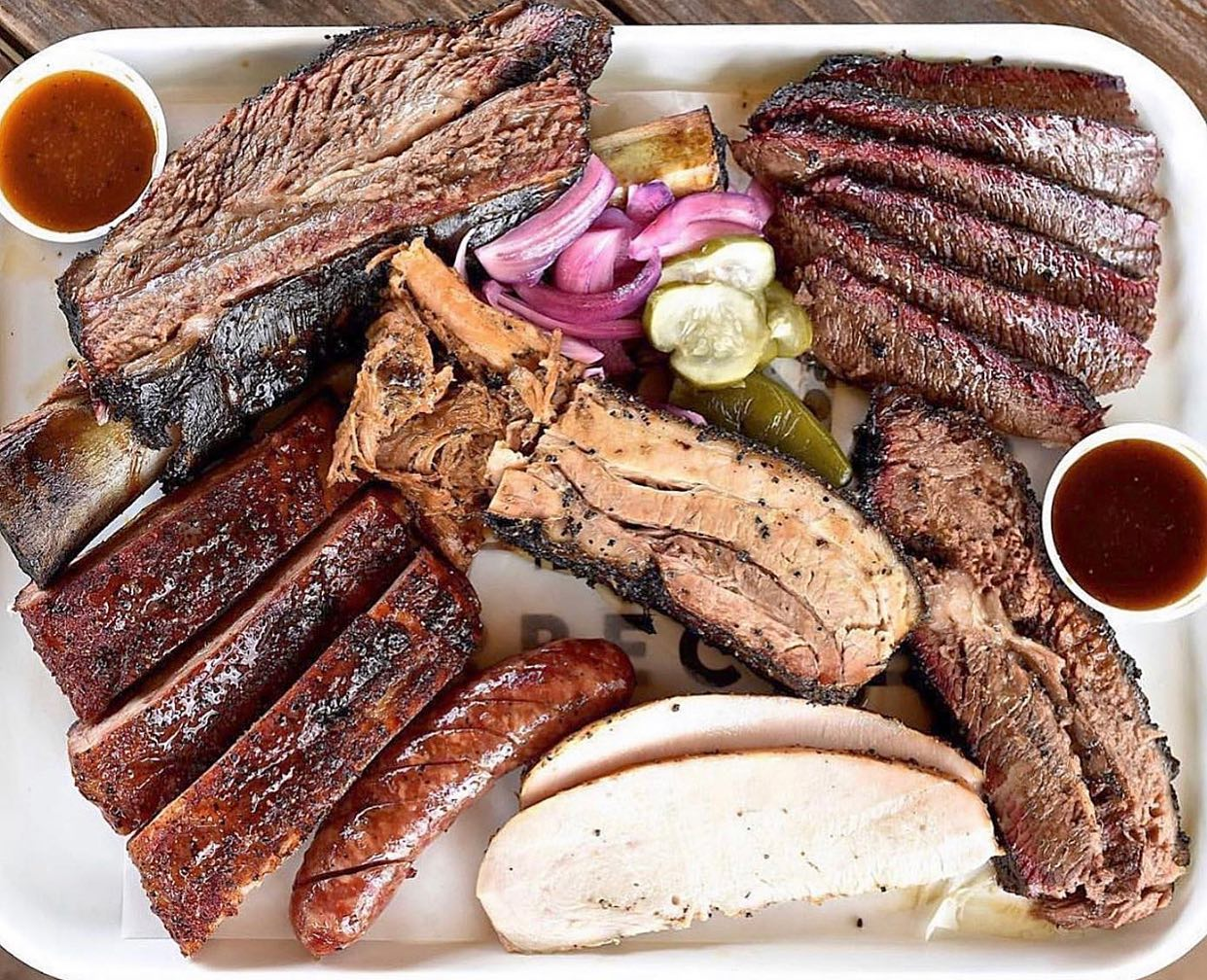 a plate of barbecue including ribs, sausage, pickles and red onions