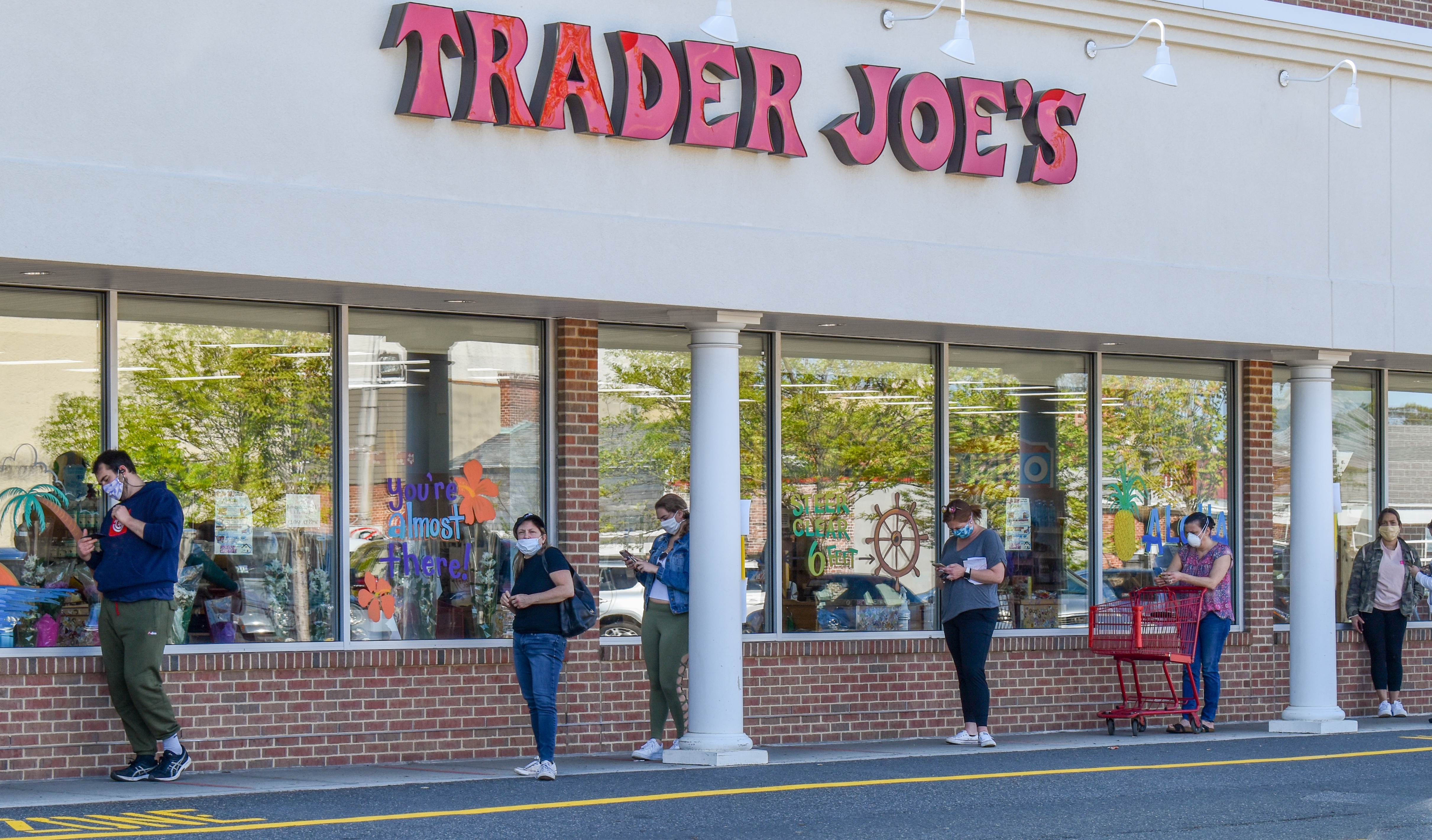 Customers with masks lined up outside of a Trader Joe's store.