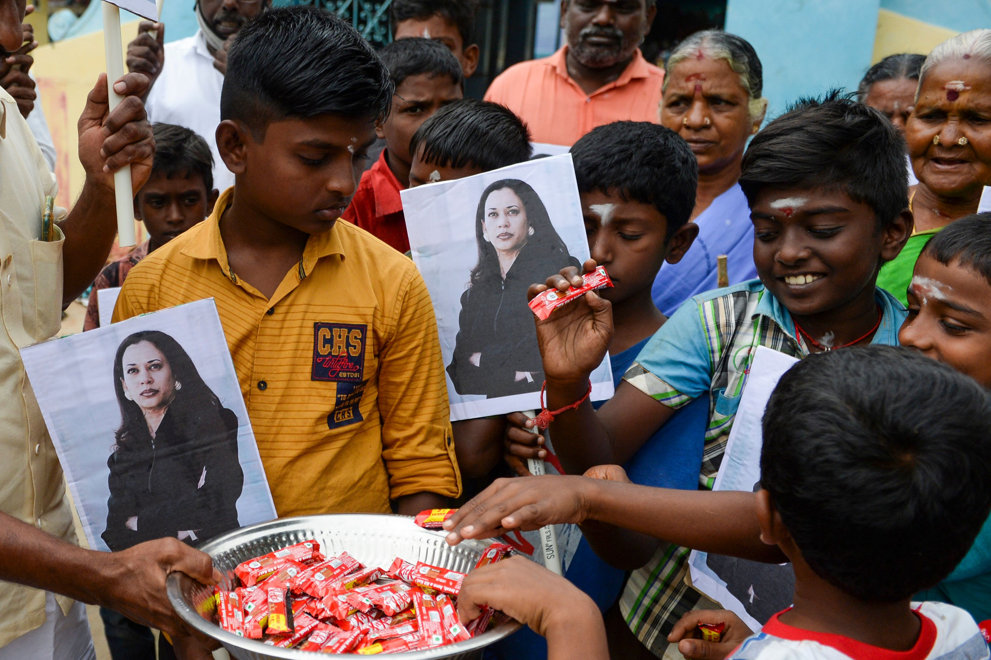 Villagers holding photos of US Vice President-elect Kamala Harris distributes sweets to celebrate at Harris' ancestral village of Thulasendrapuram in the southern Indian state of Tamil Nadu on January 20, 2021.