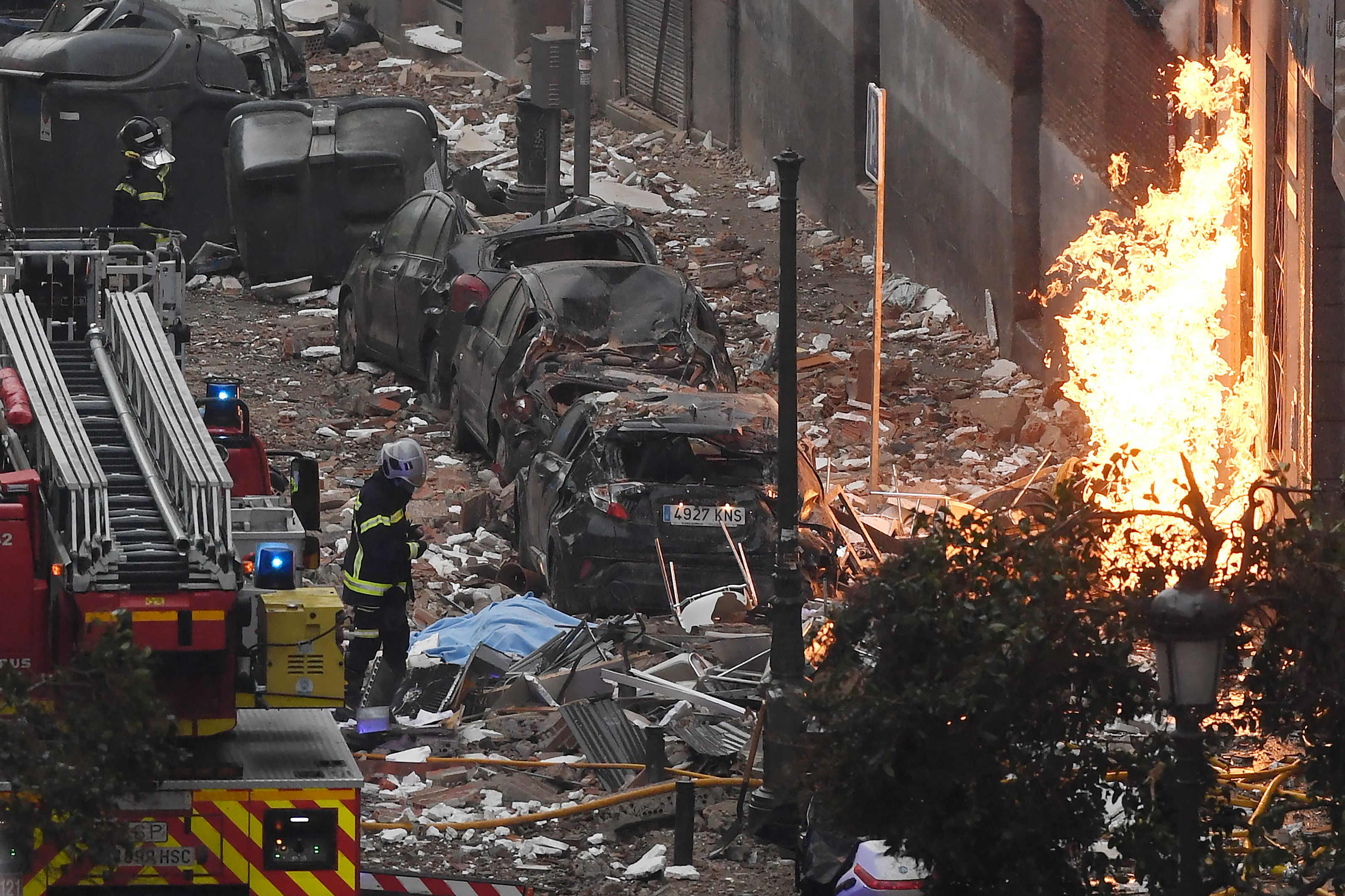 Firefighters walk outside a building in Madrid on January 20, 2021 after a strong explosion rocked it.