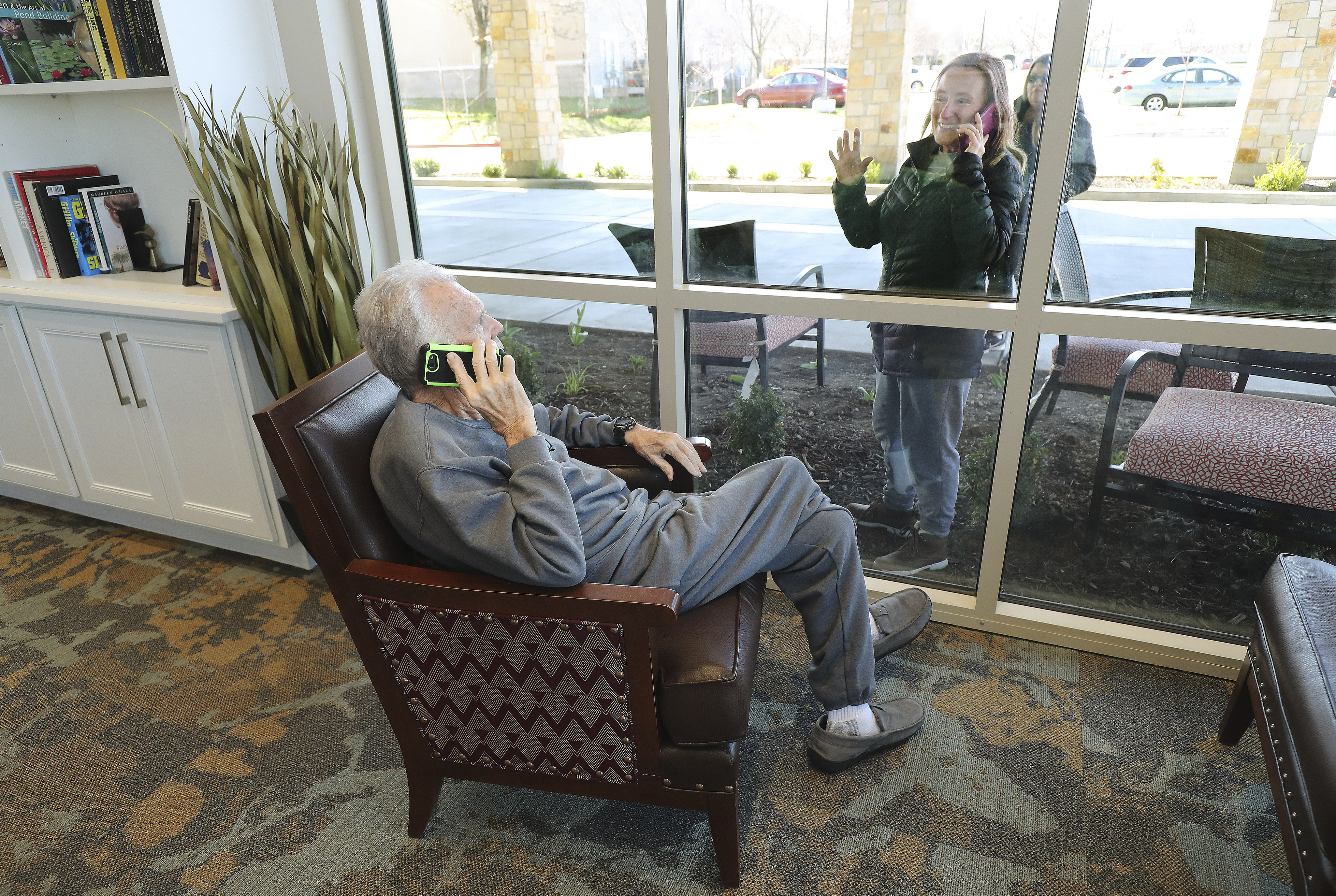 Kaye Knighton, a resident at Creekside Assisted Living and Senior Center in Bountiful, talks by cellphone to daughter-in-law Darla Knighton on Friday, March 27, 2020. Family of residents come to the window to see and talk to them via a cellphone due to Covid-19 restrictions.