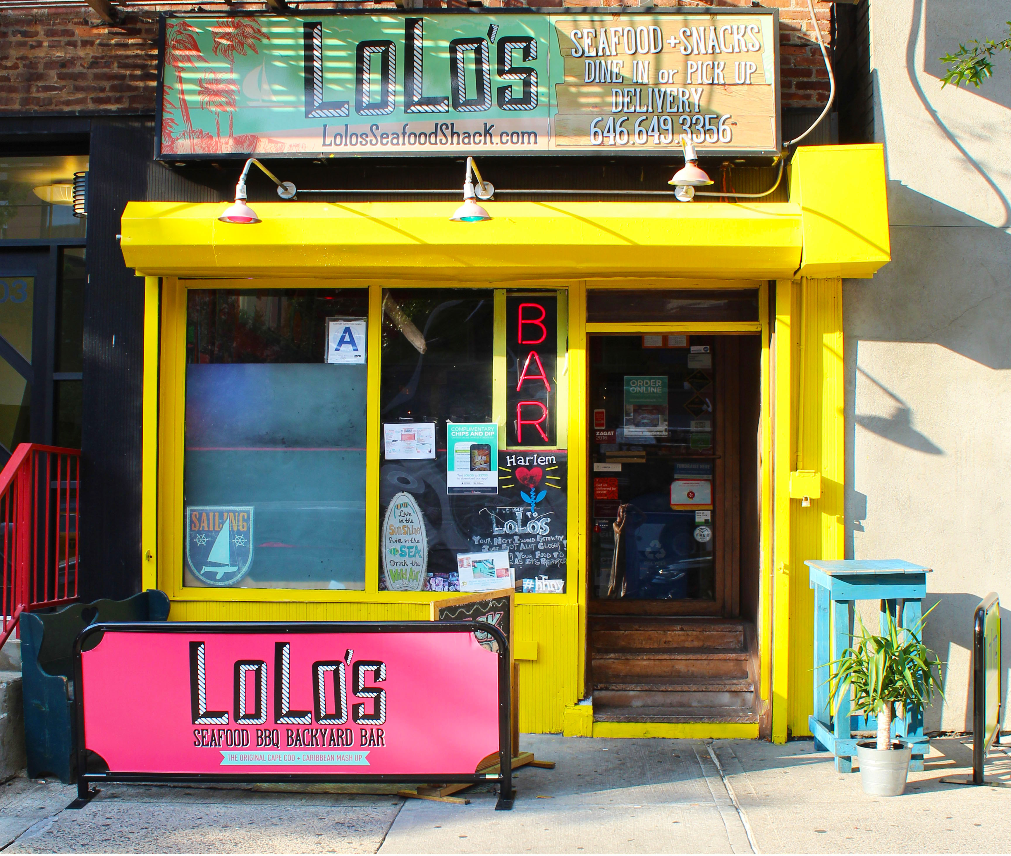 The colorful, pink and yellow storefront of a restaurant advertises takeout and delivery services