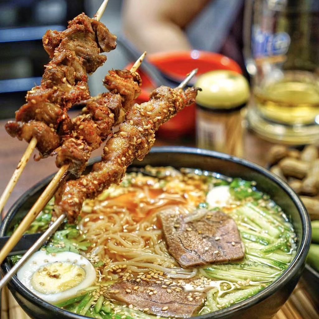 a bowl of noodles and a hand holding three barbecued meat skewers in the foreground. the meat is dusted with sesame seeds