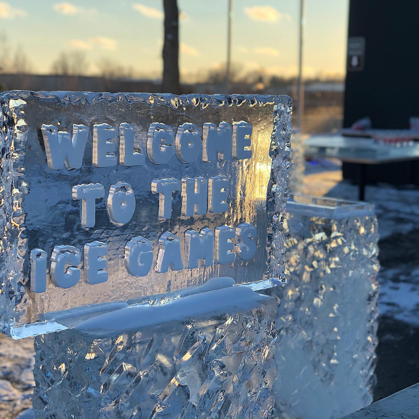 A sign made completely of ice reads Welcome to the Ice Games.