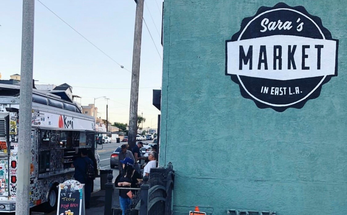 A teal side of a building with a food truck out front and customer milling about.