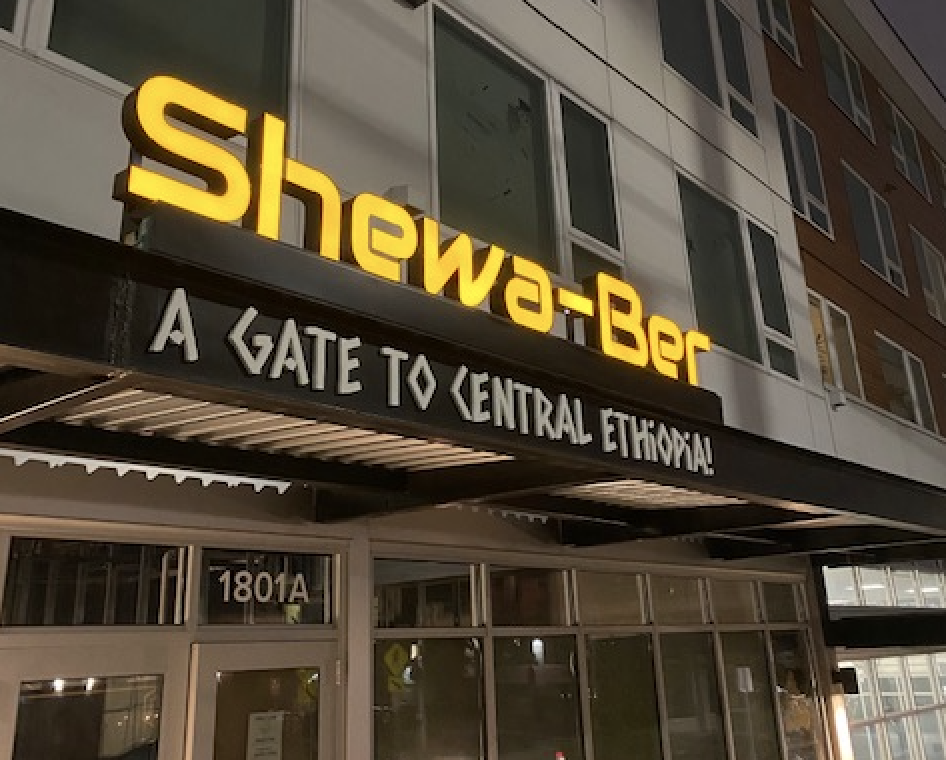 The outside of Shewa-Ber restaurant in bright yellow letters