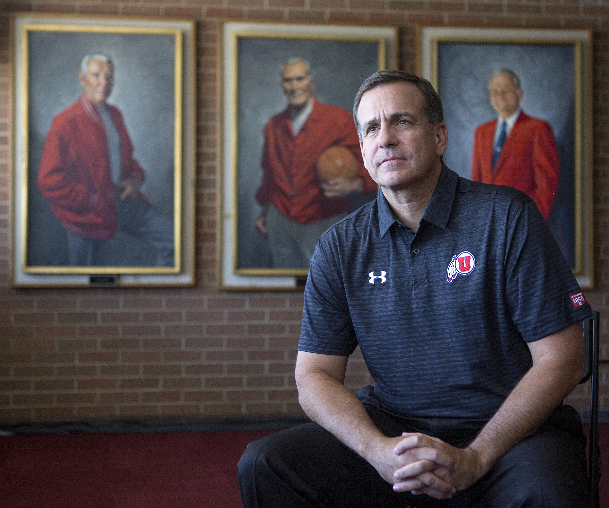 Mark Harlan, the new athletic director at the University of Utah, poses in front of portraits of former athletic director Isaac Armstrong, left, former head basketball coach Vadal Peterson and former athletic director James Jack at the Huntsman Center in Salt Lake City on Friday, June 29, 2018.