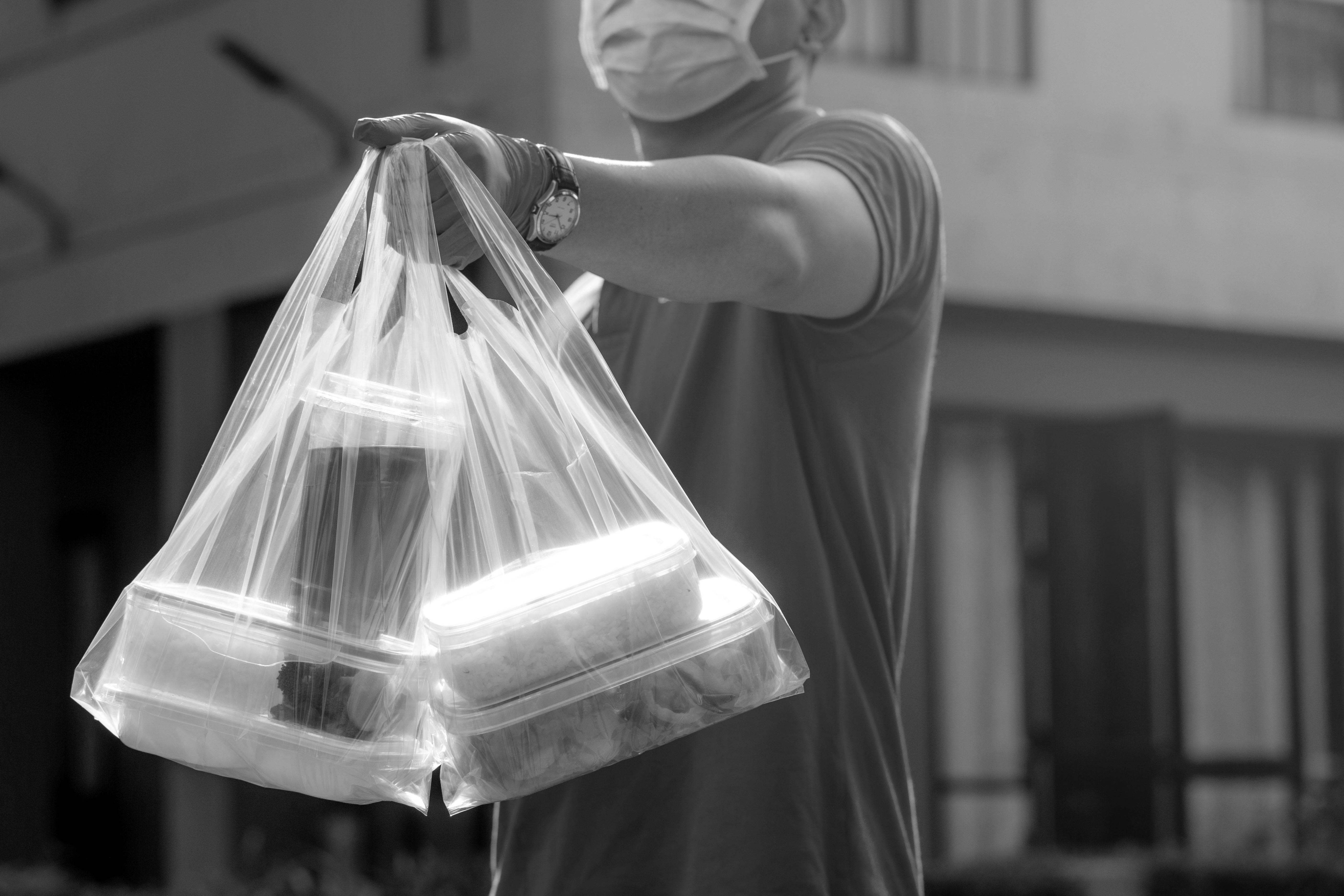 A black and white image of a clear bag containing four full takeout containers and a drink.