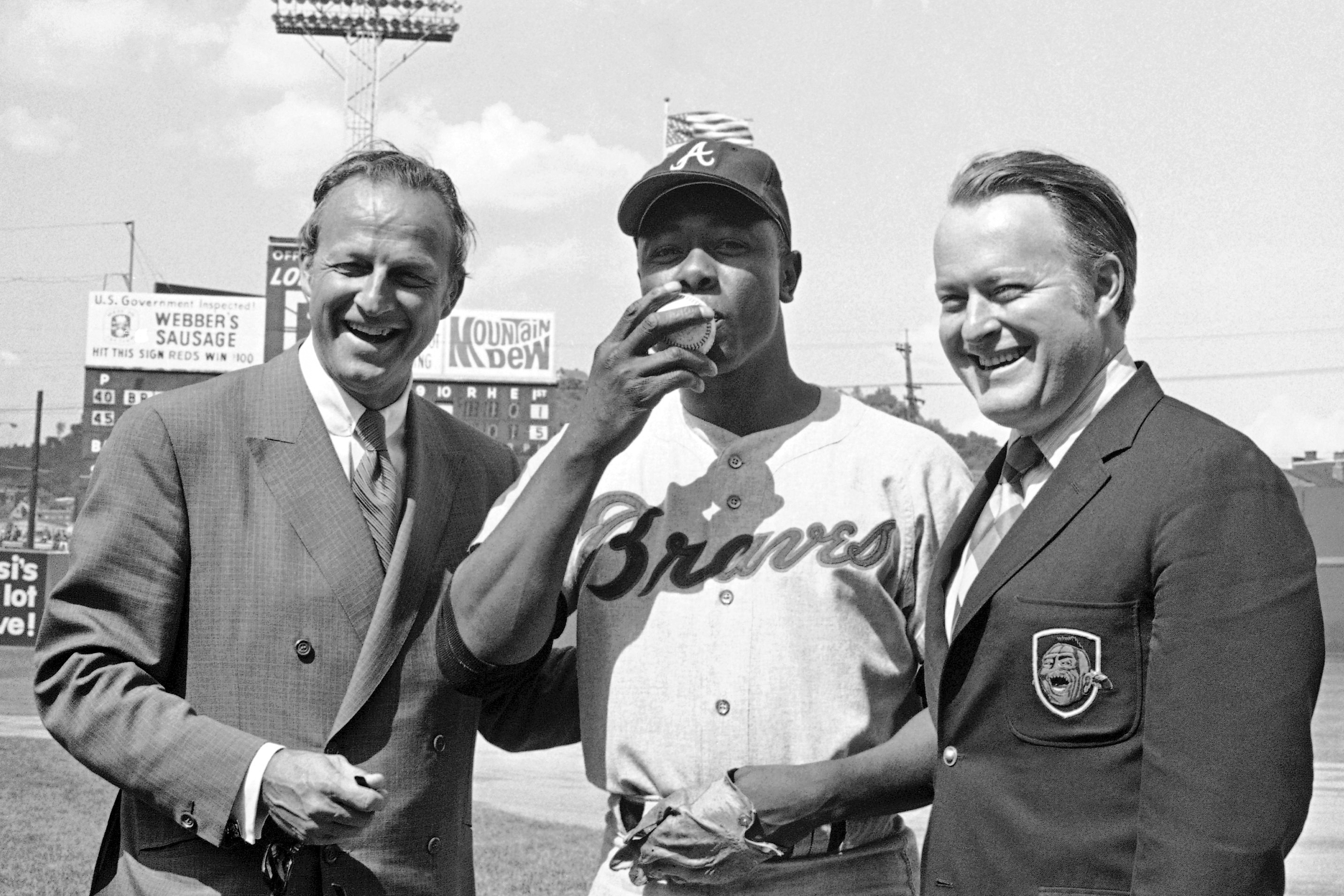 In this May 17, 1970, file photo, Atlanta Braves' Hank Aaron, center, who became the ninth player in Major League history to get 3,000 hits, kisses a baseball alongside Famer Stan Musial and Braves owner Bill Bartholomay, in Cincinnati.