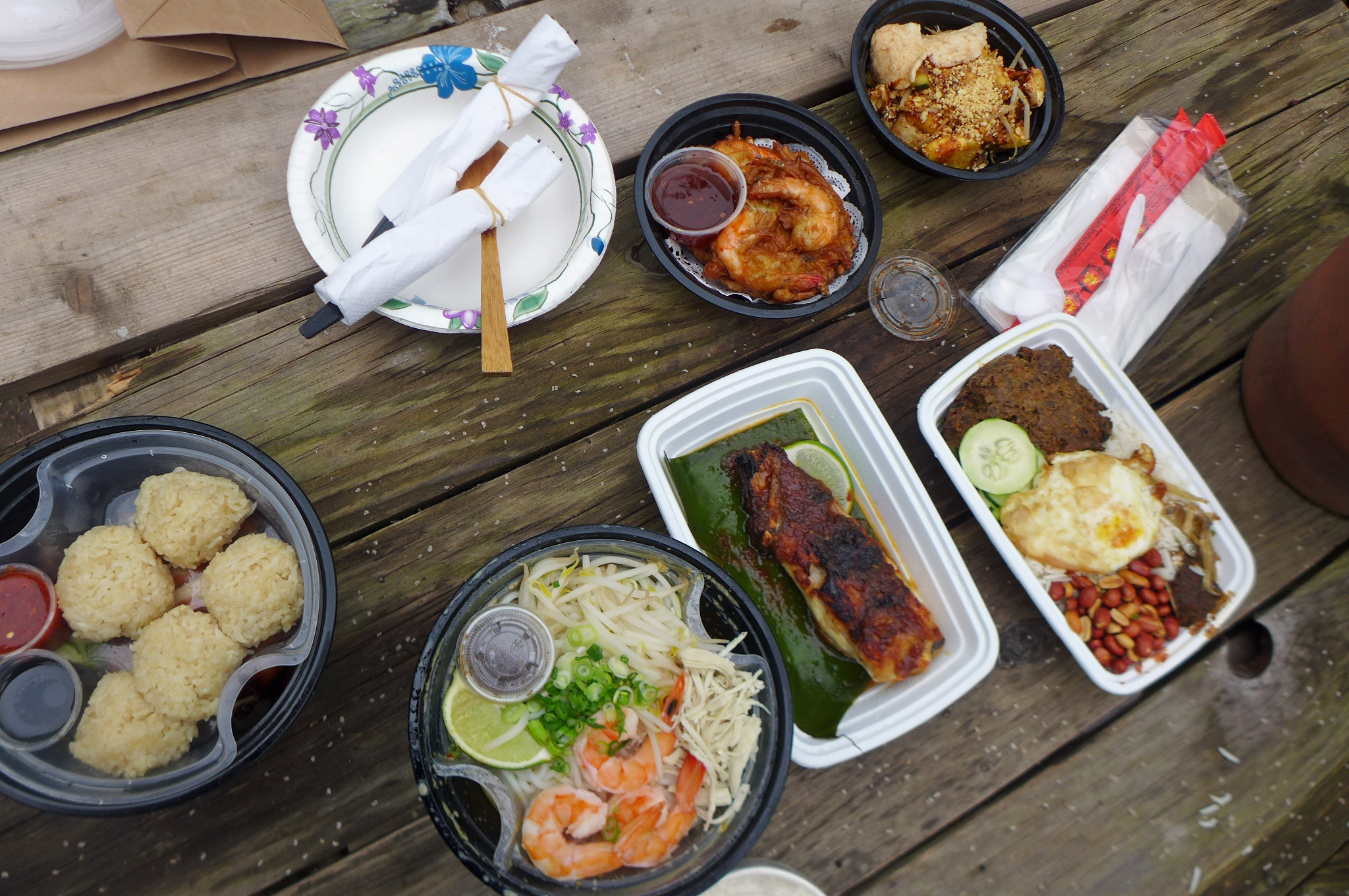 Several Malaysian dishes, including chicken and rice, shrimp fritters, and stingray, along with plates, plastic utensils, and  chopsticks on a wooden table outdoors.