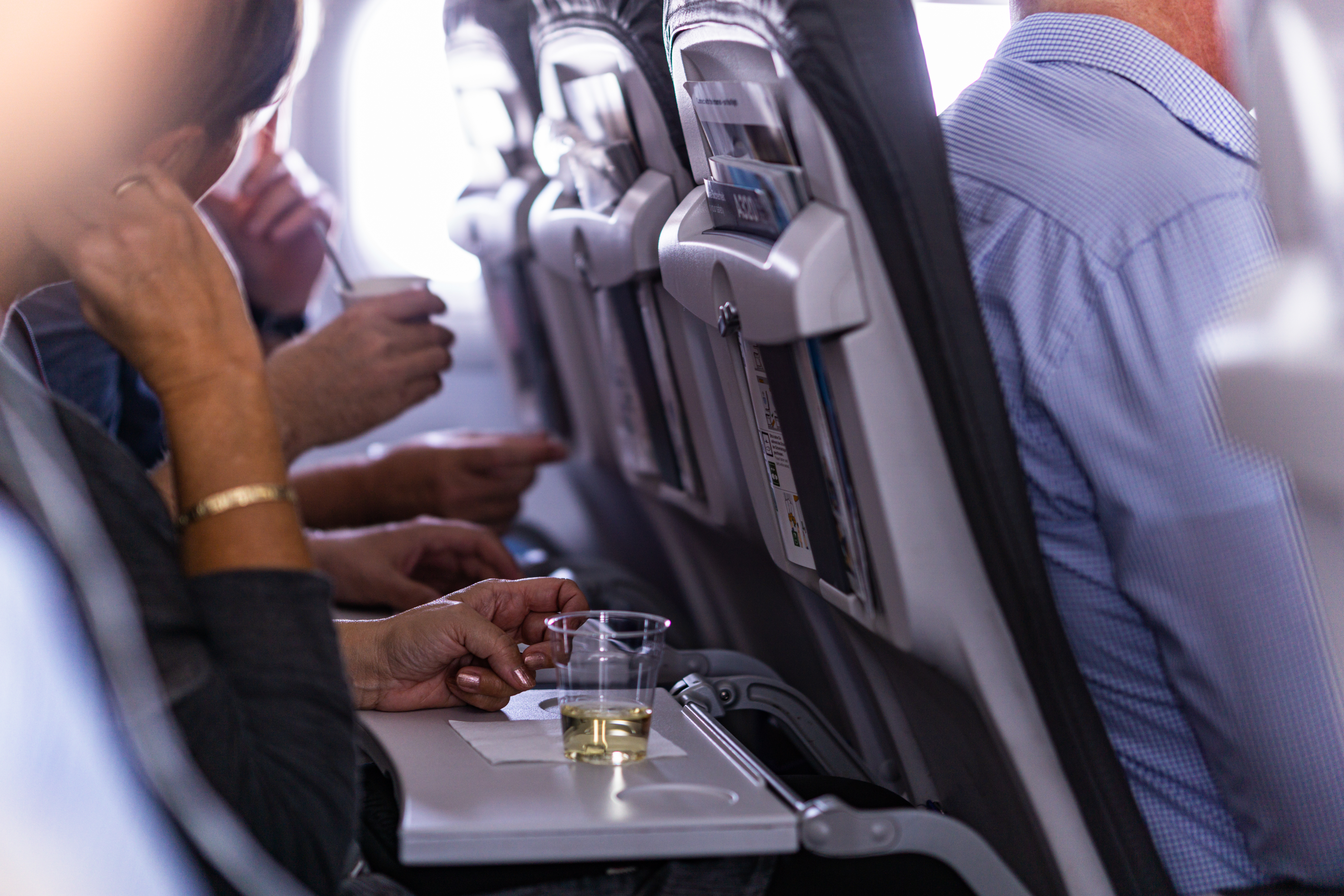 People sit in a cramped row of an airplane with the seat-back tables down and a plastic cup of white wine in the foreground.