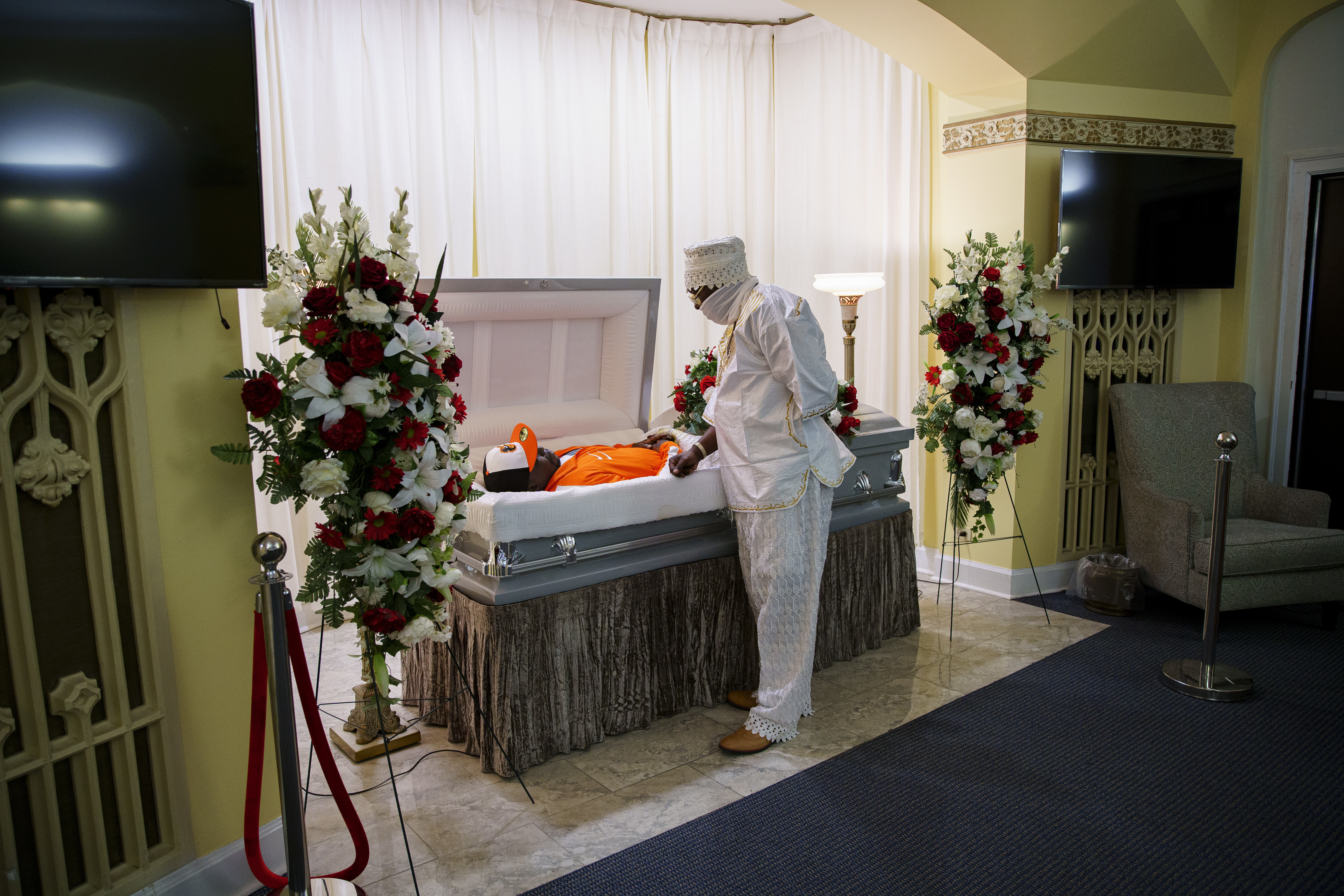 Olumide Olupitan looks down at the body of his brother Oyedele Olupitan at his visitation Sept. 5 at Sacred Memories Funeral Home in South Shore. Oyedele Olupitan, 42, had been shot in the head on Aug. 18 in Washington Heights on the South Side.