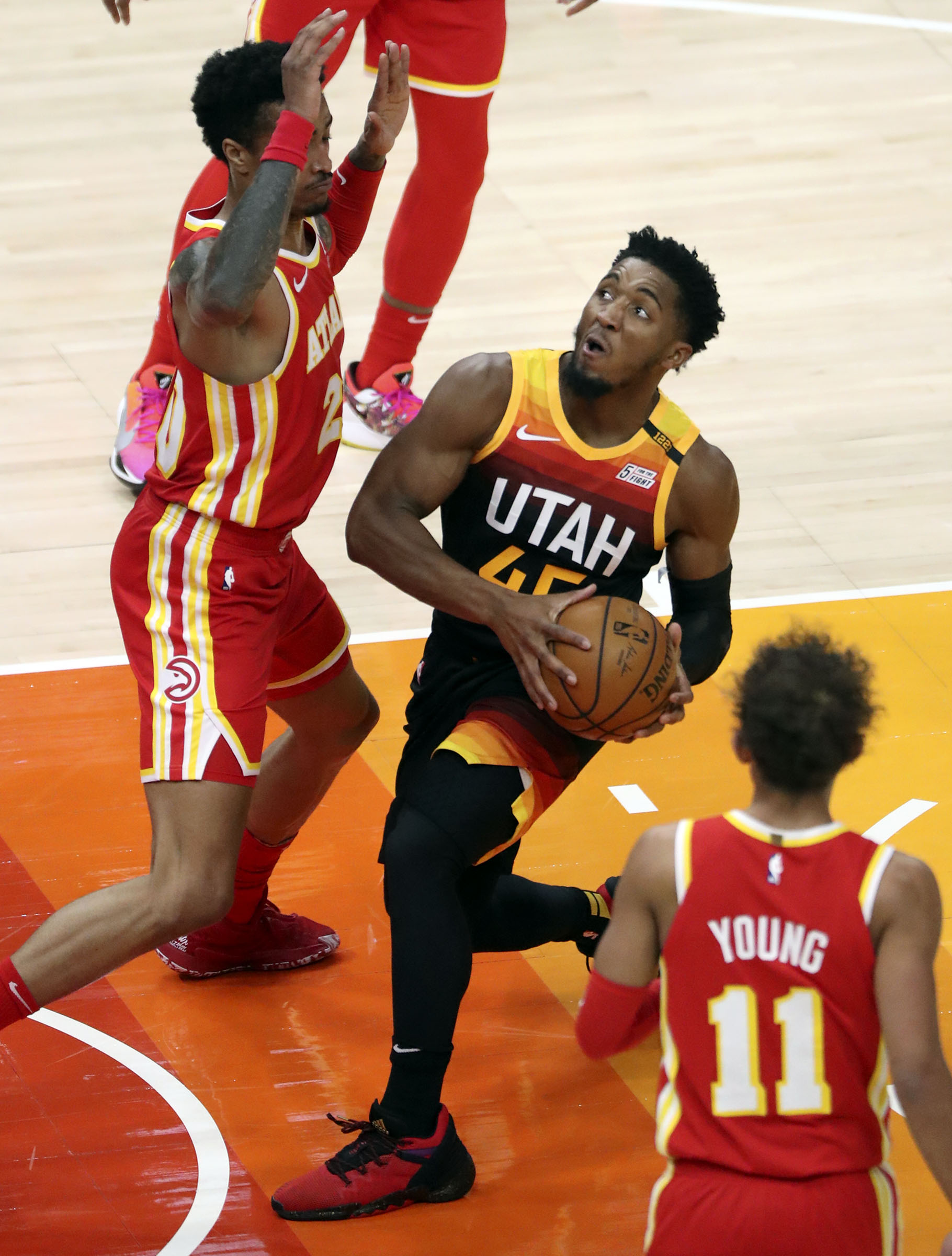 Utah Jazz guard Donovan Mitchell (45) looks to make a shot between Atlanta Hawks forward John Collins (20) and Atlanta Hawks guard Trae Young (11) during an NBA game at Vivint Smart Home Arena in Salt Lake City on Friday, Jan. 15, 2021. The Jazz won 116-92.