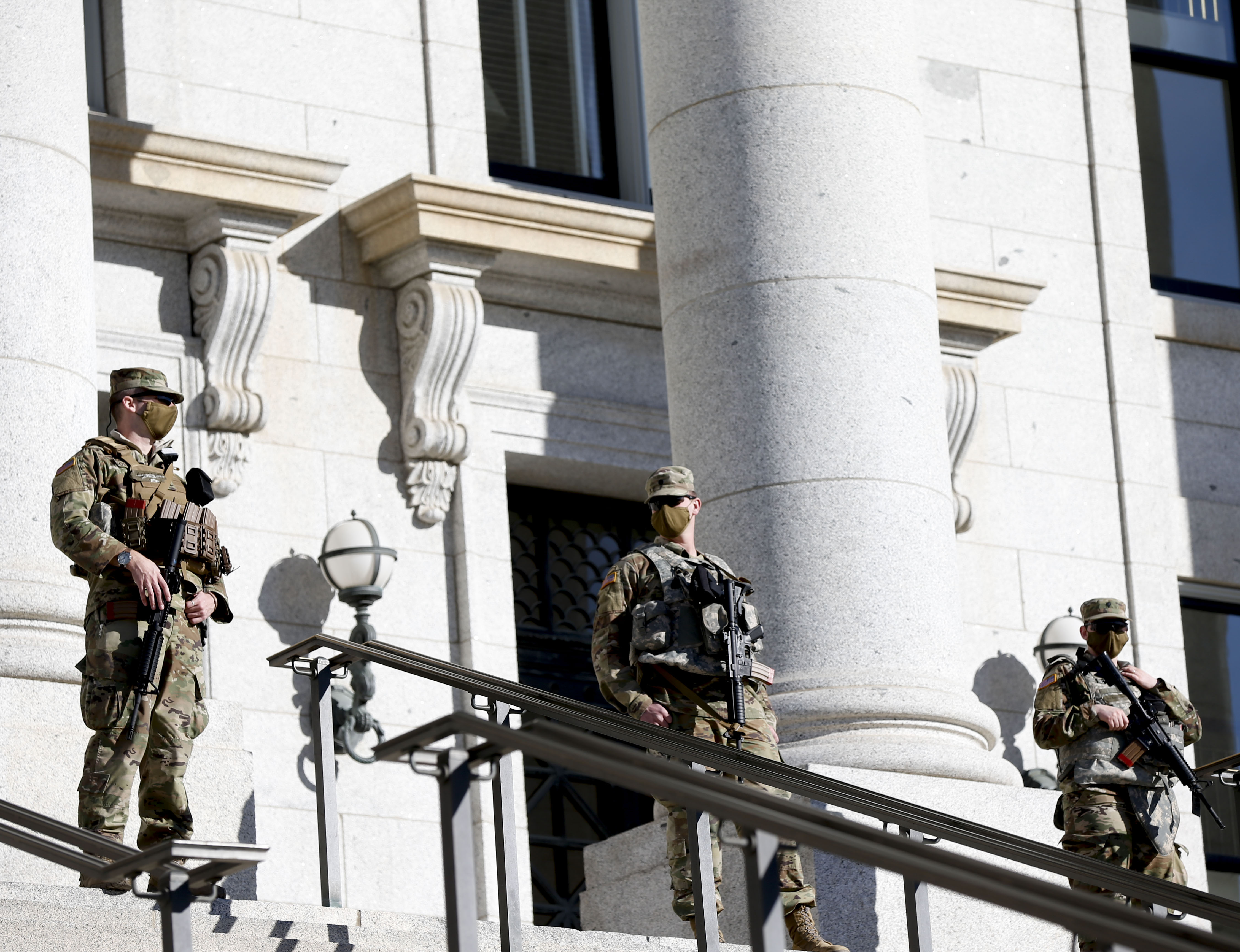 Armed Utah National Guard soldiers patrol the state Capitol in Salt Lake City on Wednesday, Jan. 20, 2021.
