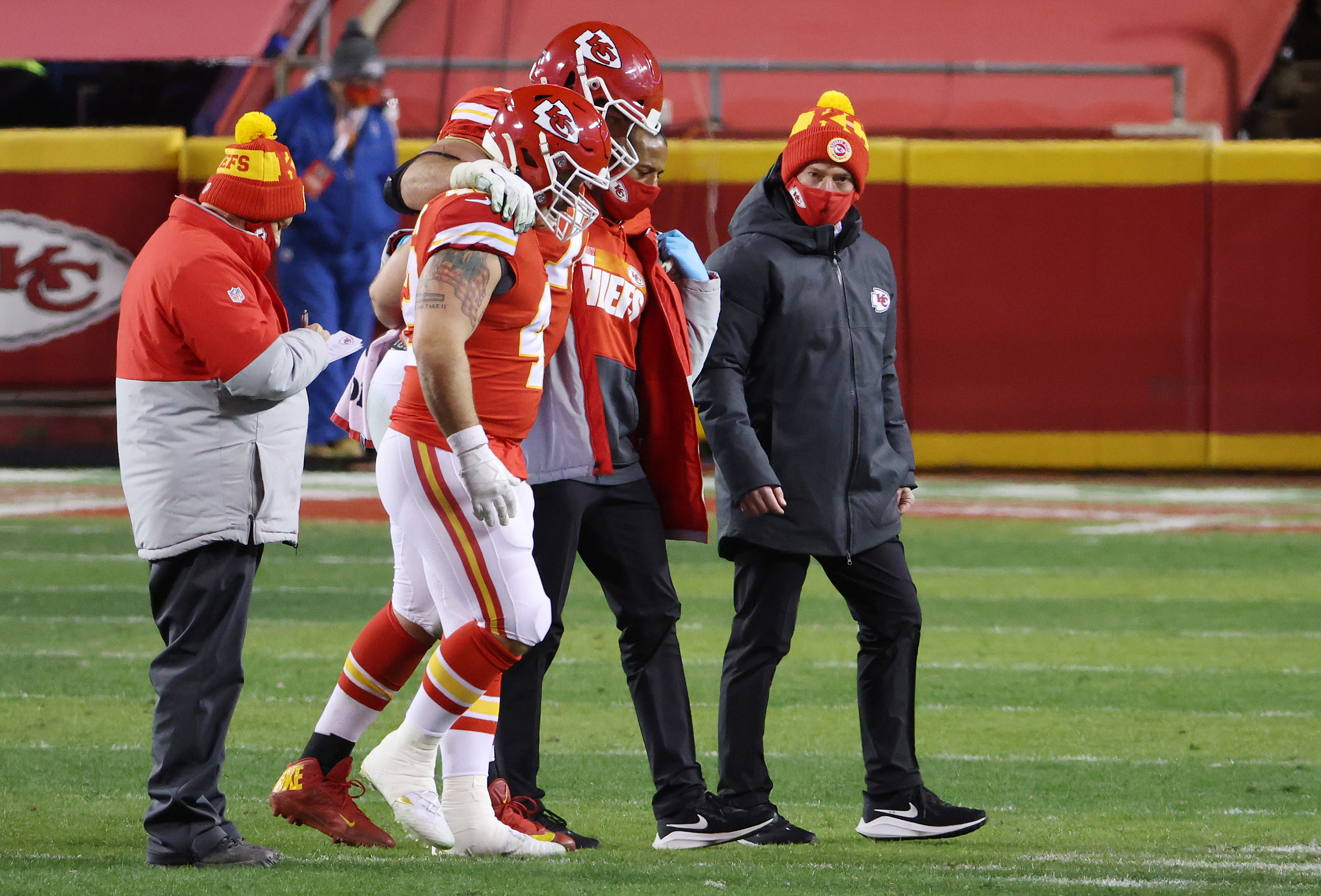 Eric Fisher #72 of the Kansas City Chiefs is helped off the field in the fourth quarter against the Buffalo Bills during the AFC Championship game at Arrowhead Stadium on January 24, 2021 in Kansas City, Missouri.