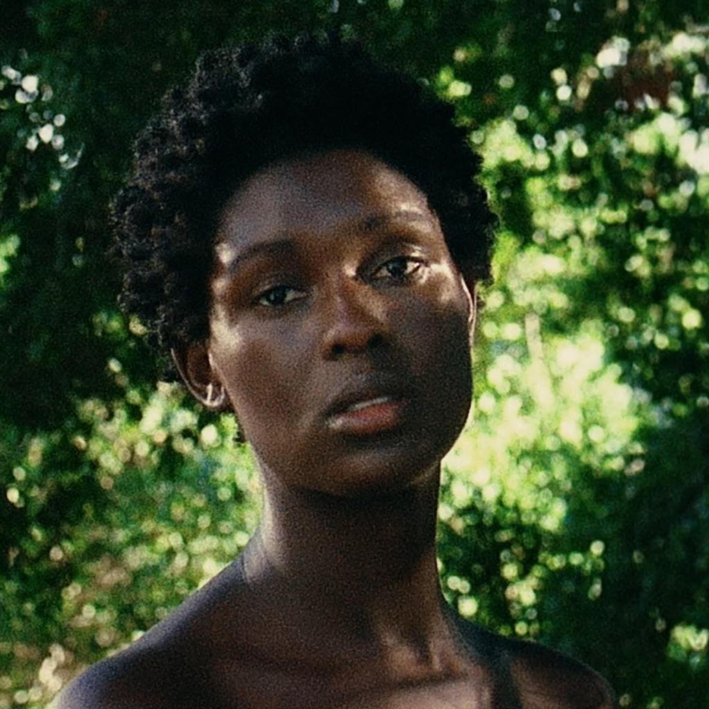 Portrait of Jodie Turner-Smith against sunbaked trees