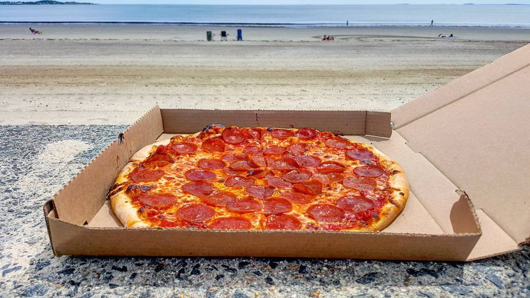 A pepperoni pizza sits in an open cardboard pizza box on a stone surface, with a mostly empty beach visible in the background