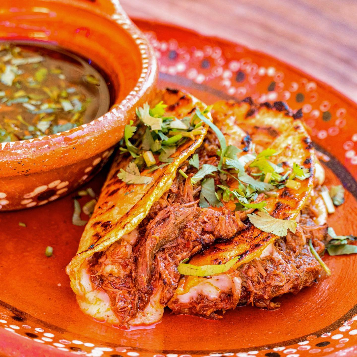A trio of birria tacos served on an orange plate. A bowl of consomme sits in the background.