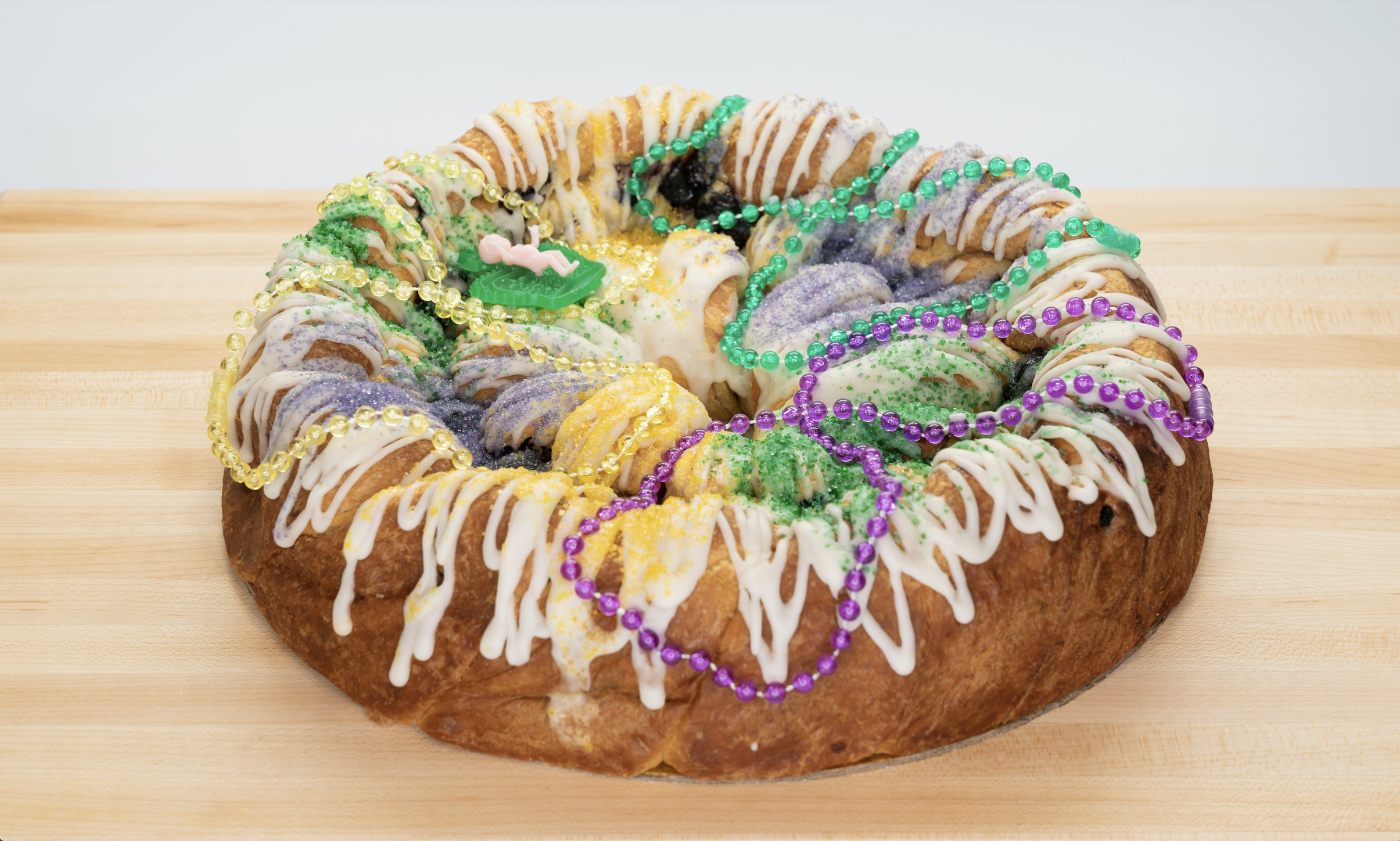 a round king cake with yellow, purple and green icing and draped with mardi gras beads