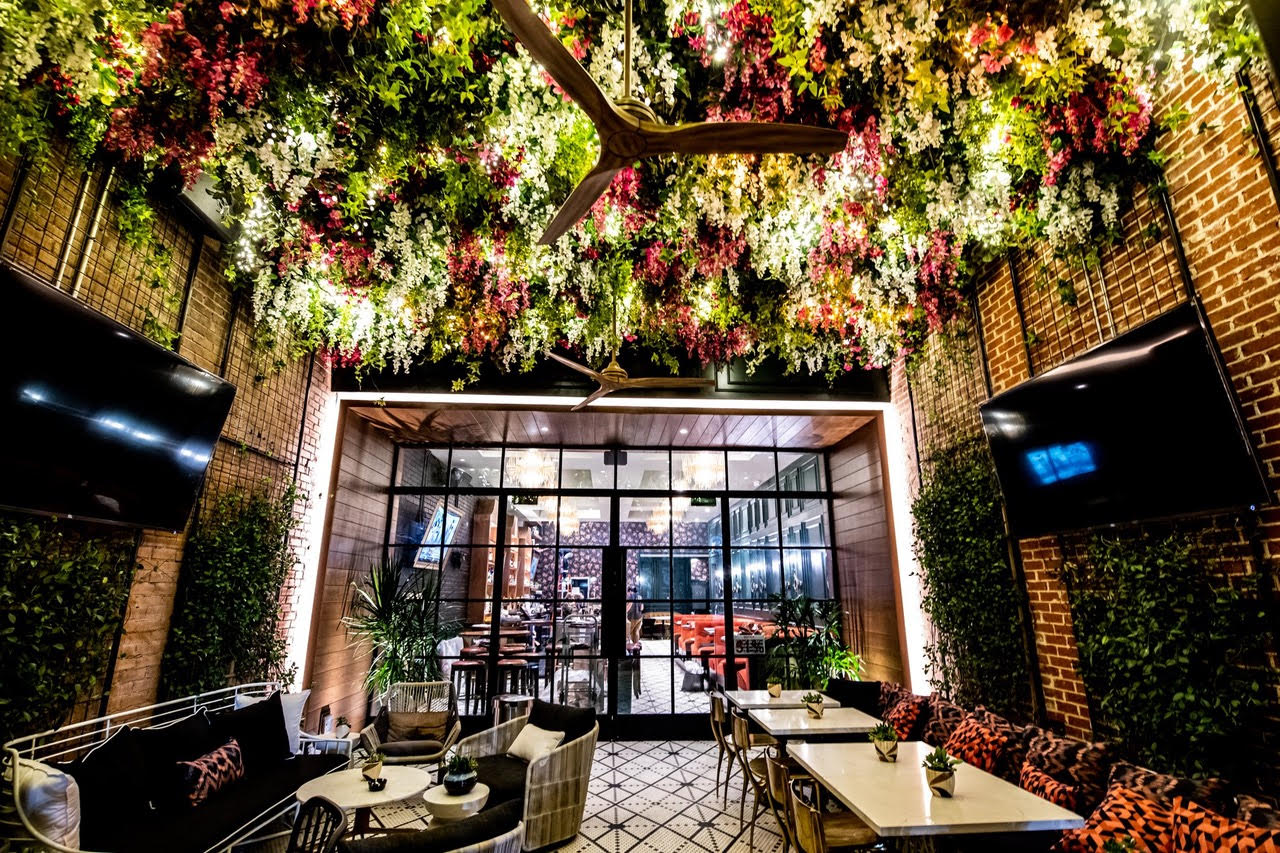 A patio space with lush greenery hanging from the ceiling, glassed doors, and tables with chairs