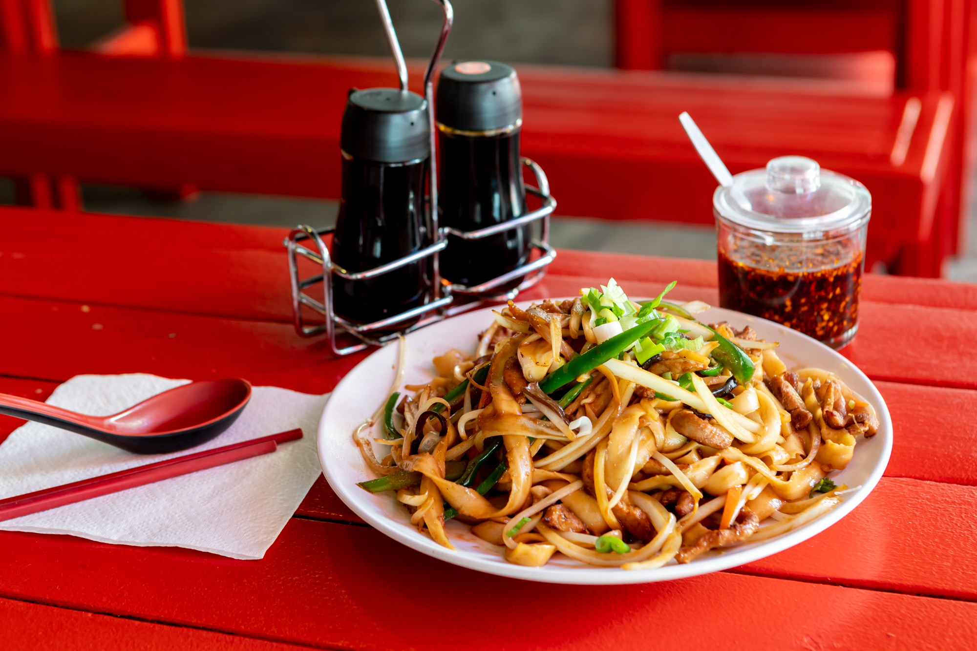 A plate of knife-cut noodles on a red table with soy sauce dispensers and chile sauce on the side