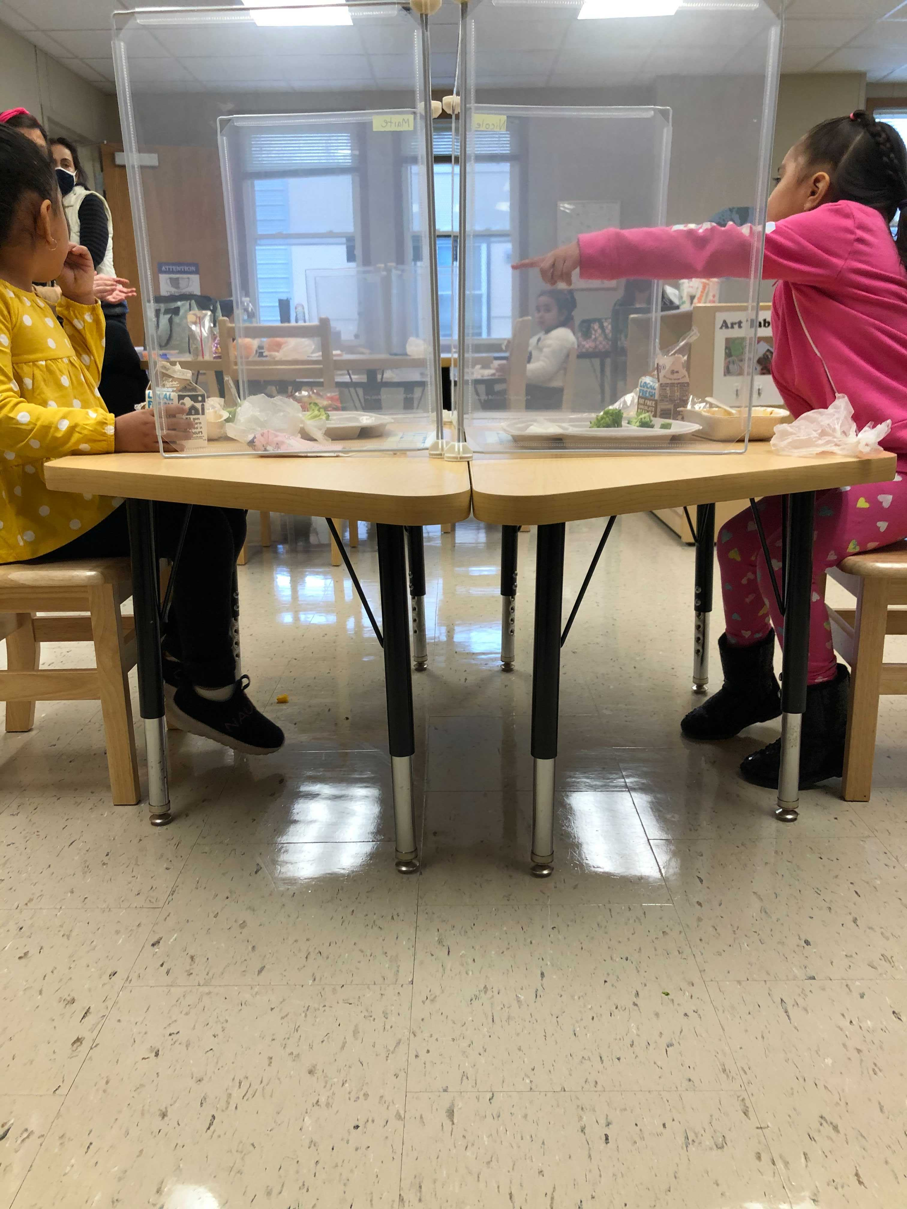Pre-kindergarten students eat lunch at their desks under new COVID-19 rules in Chicago schools.