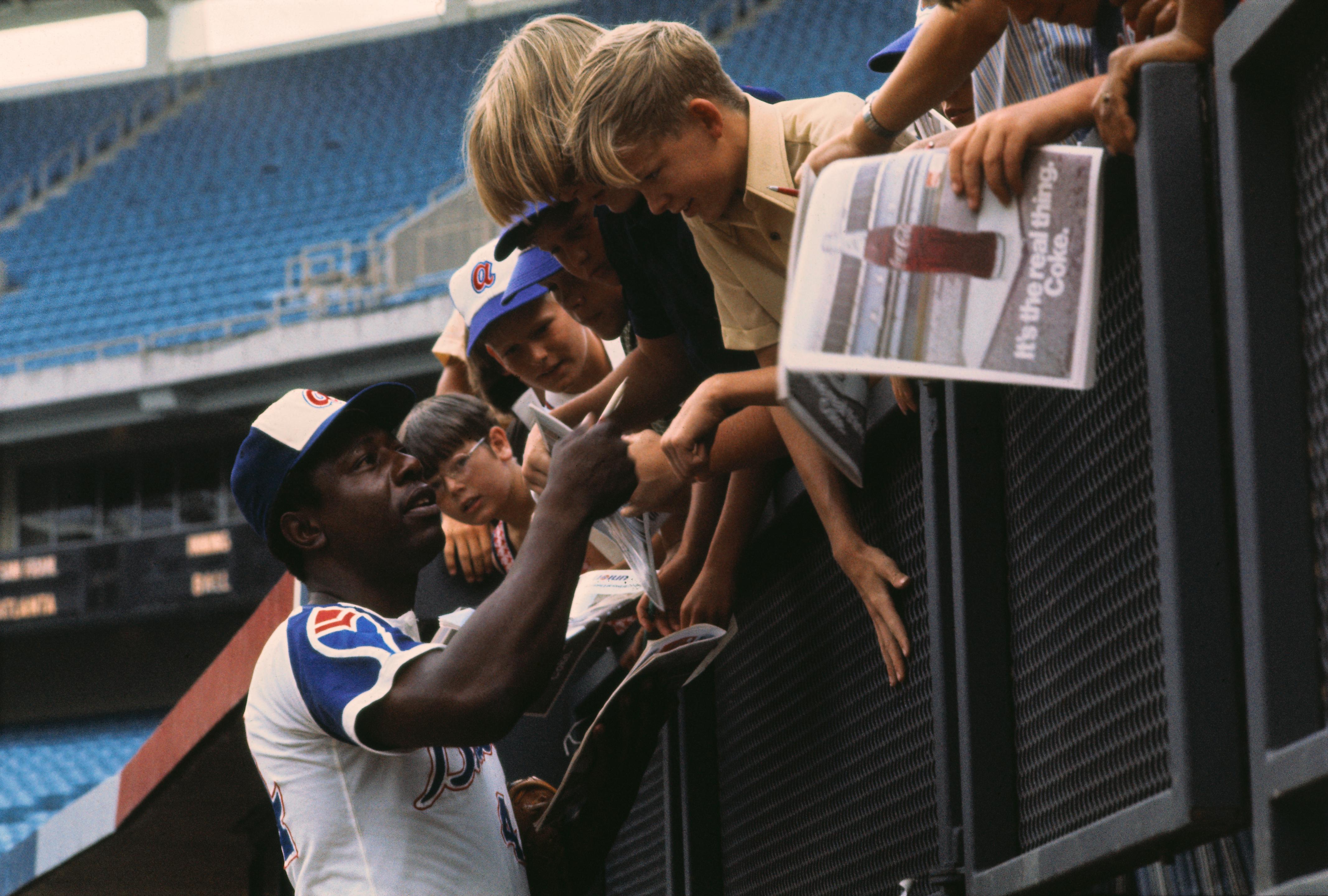 Hank Aaron Signing Autographs for Children in Stadium
