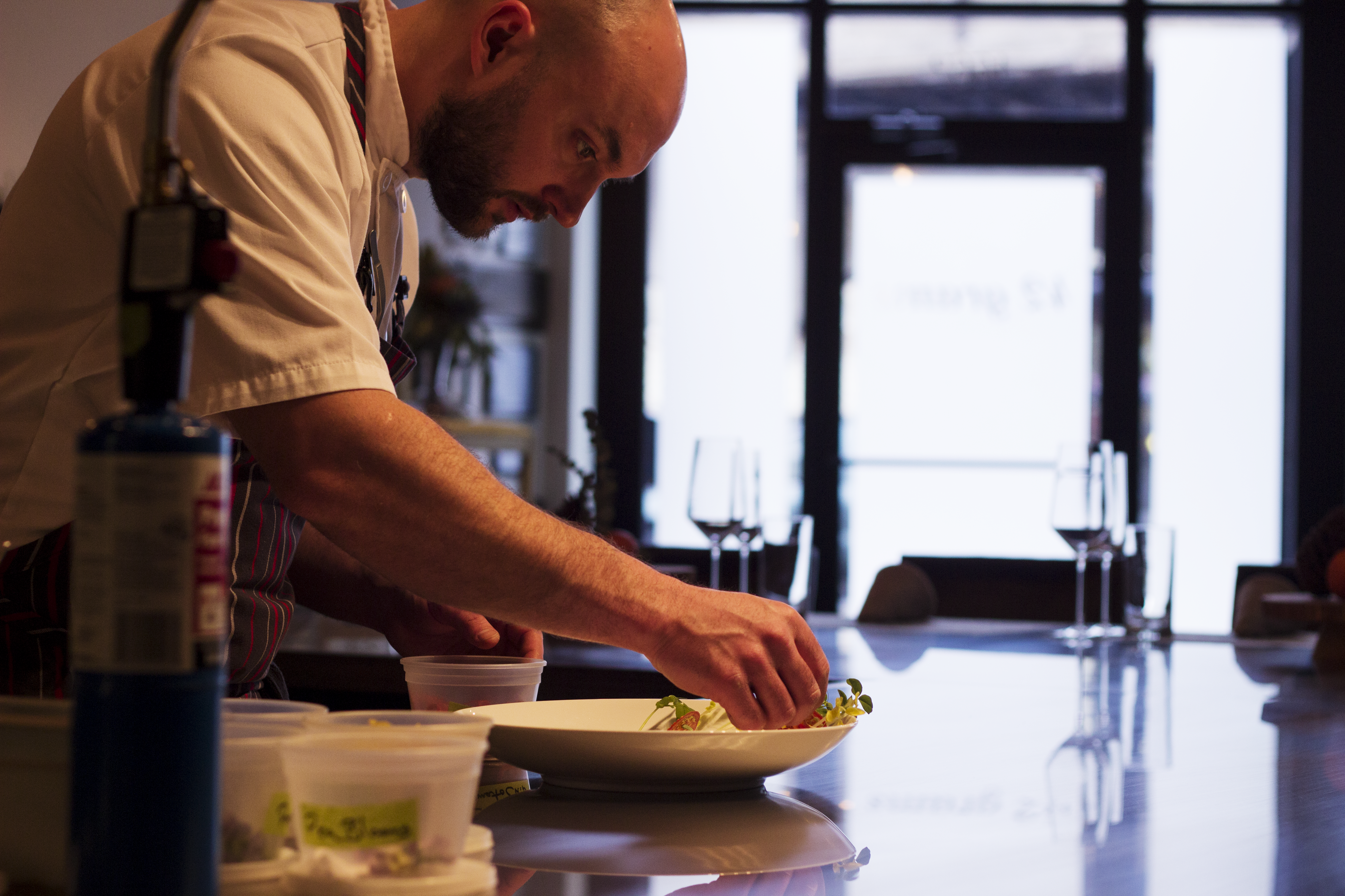 A chef bent over, plating food into a shallow bowl.