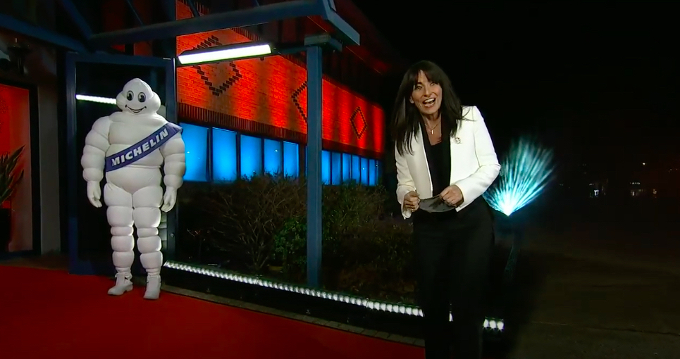 Davina McCall stands on a red carpet looking into the camera, while the Michelin man stands awkwardly in the background