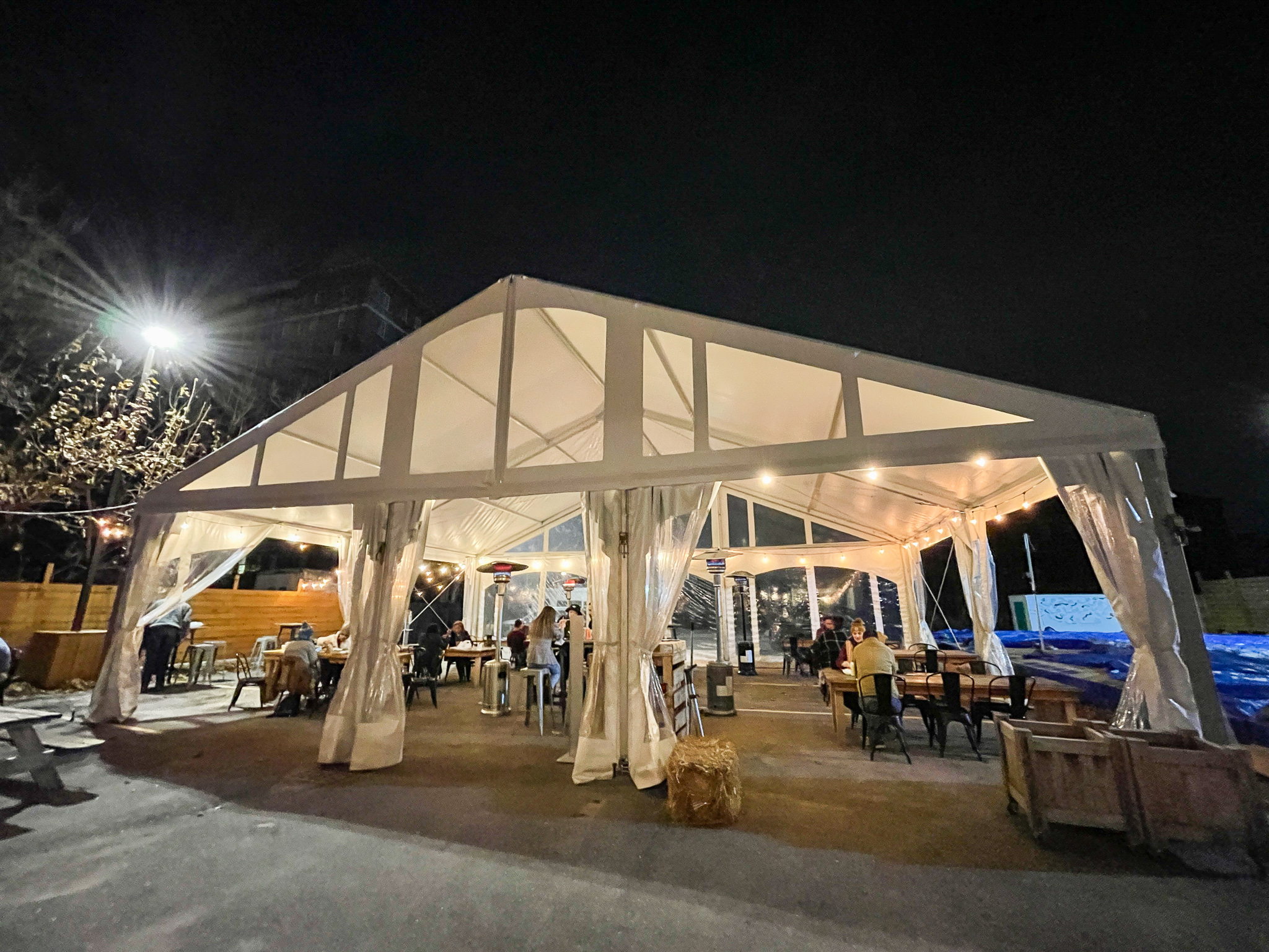 Detroit Shipping Company's outdoor dining set up with a large white tent, heaters, and tables.