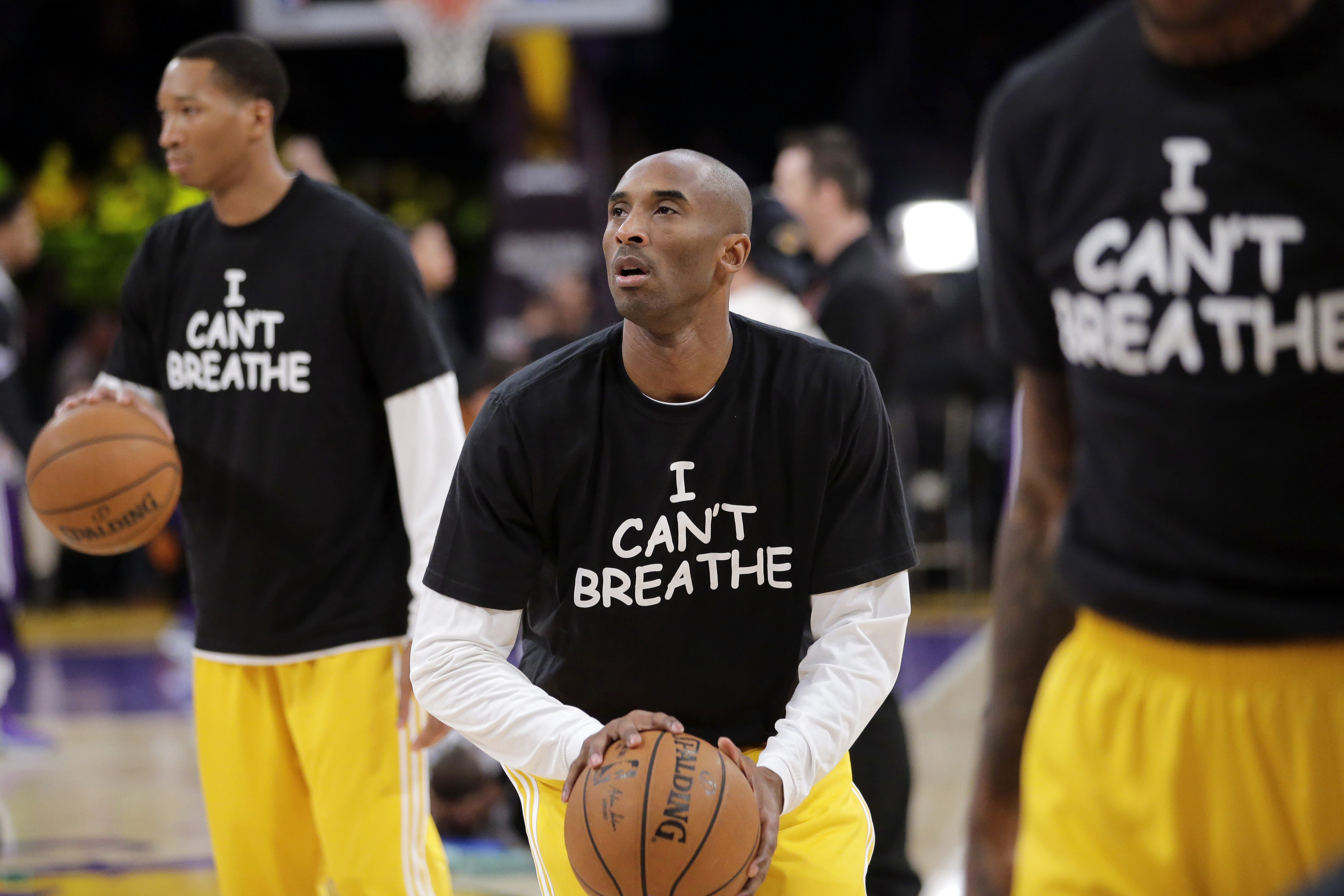 """In this Dec. 9, 2014, file photo, Los Angeles Lakers' Kobe Bryant, center, warms up before an NBA basketball game against the Sacramento Kings in Los Angeles. Dozens of athletes in recent weeks have responded to confrontations between authorities and black citizens in Ferguson, Mo., New York and elsewhere by wearing T-shirts bearing such statements as """"I Can't Breathe"""" and """"Hands Up, Don't Shoot!"""" (AP Photo/Jae C. Hong, File)"""