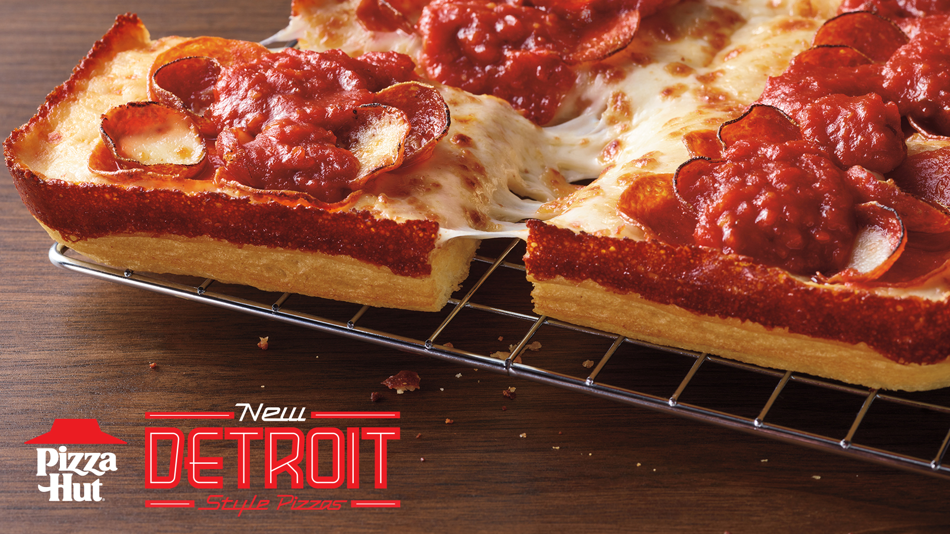 Close-up of a Detroit-style pizza with caramelized crust, cheese, pepperoni, and tomato sauce on top.