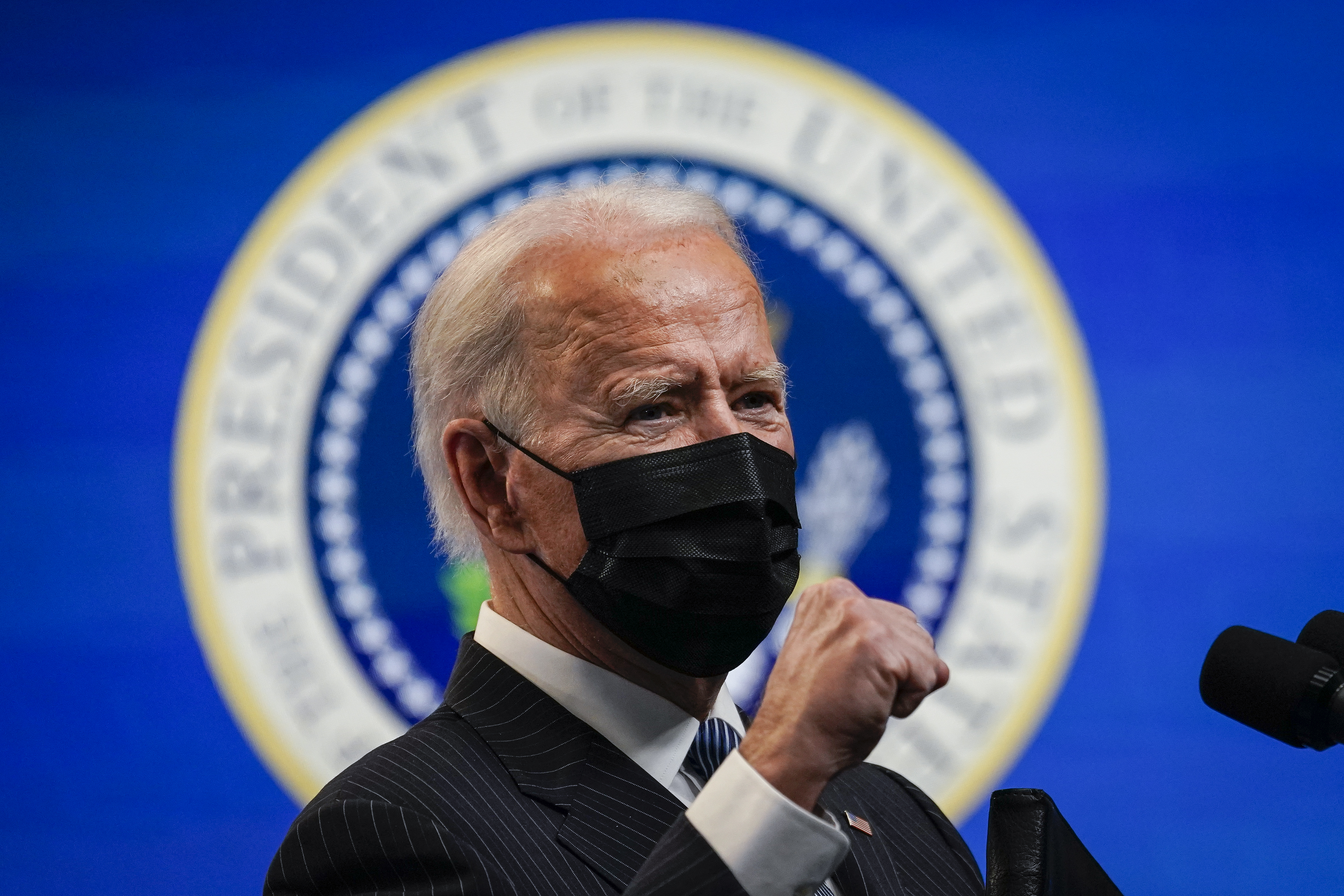 President Joe Biden wears a mask and holds a fist in front of him while speaking at a White House event.