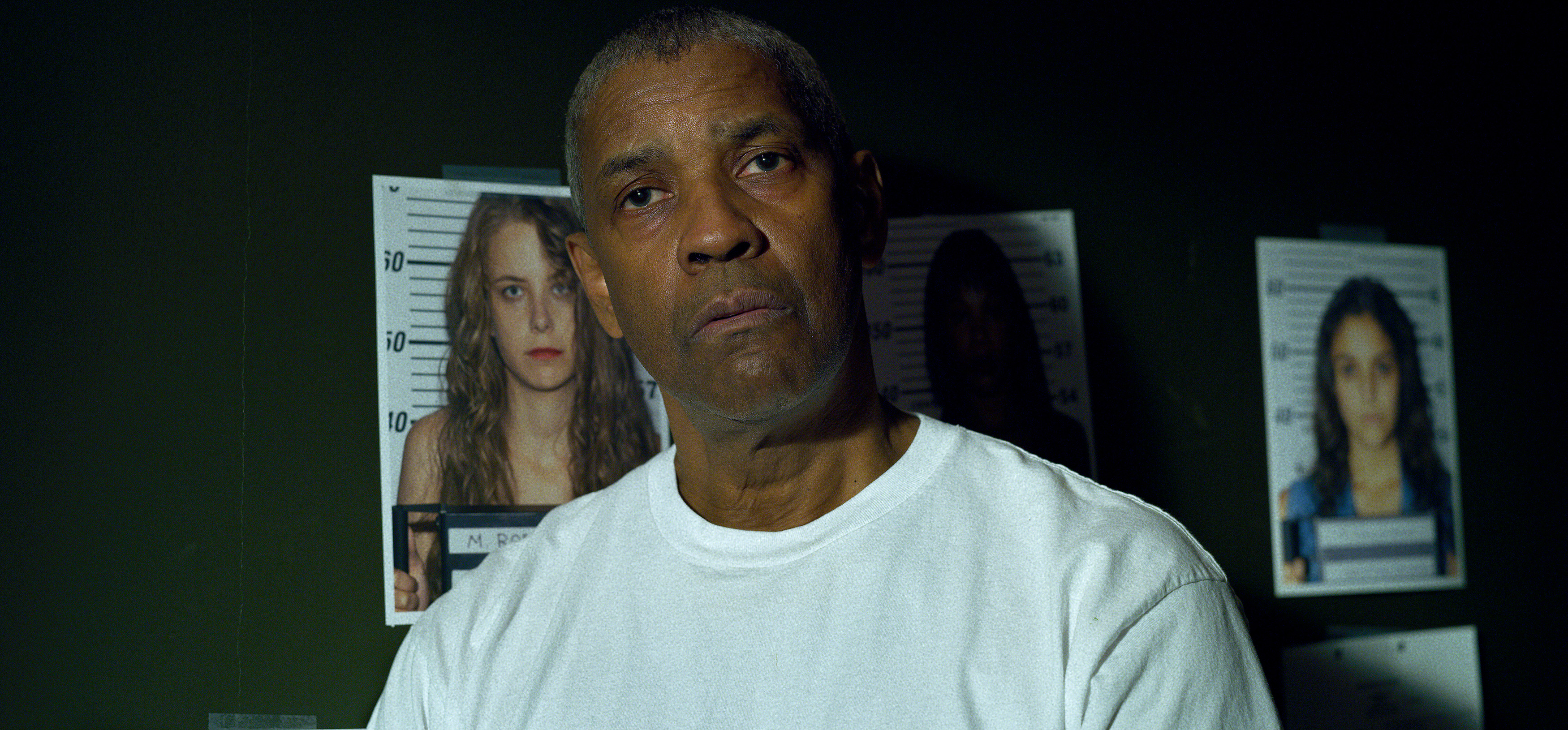 Denzel Washington wears a white t-shirt and stands in front of a green wall with pictures of murdered women in The Little Things
