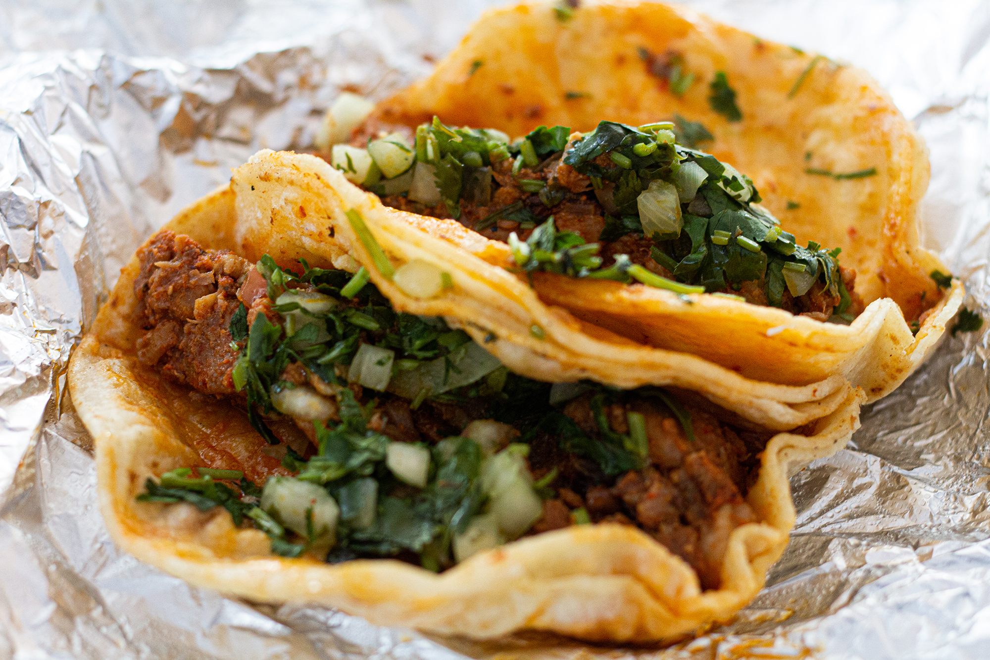 Two tacos packed with pork, pineapple, cilantro, and onion, wrapped with aluminum foil