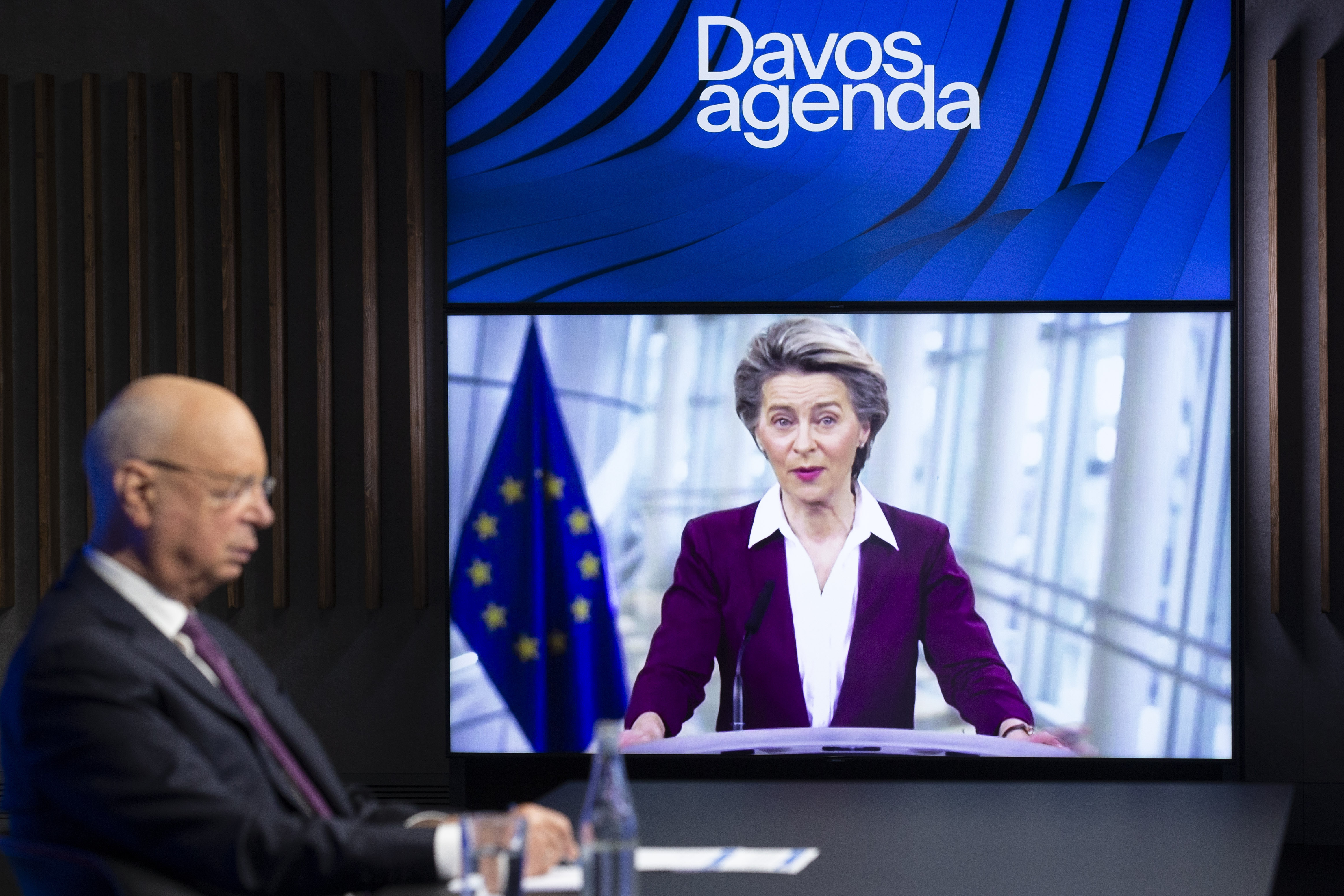 German Klaus Schwab, left, Founder and Executive Chairman of the World Economic Forum, WEF, listens to European Commission President Ursula von der Leyen, displayed on a video screen, during a conference at the Davos Agenda in Cologny near Geneva, Switzerland, Tuesday, Jan. 26, 2021.