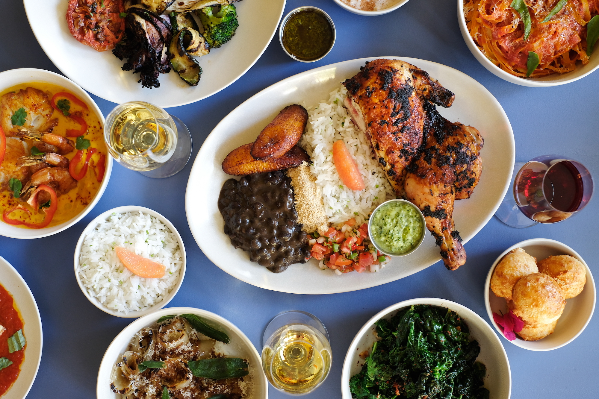 A roasted half chicken plate with rice and plantains shot from above.