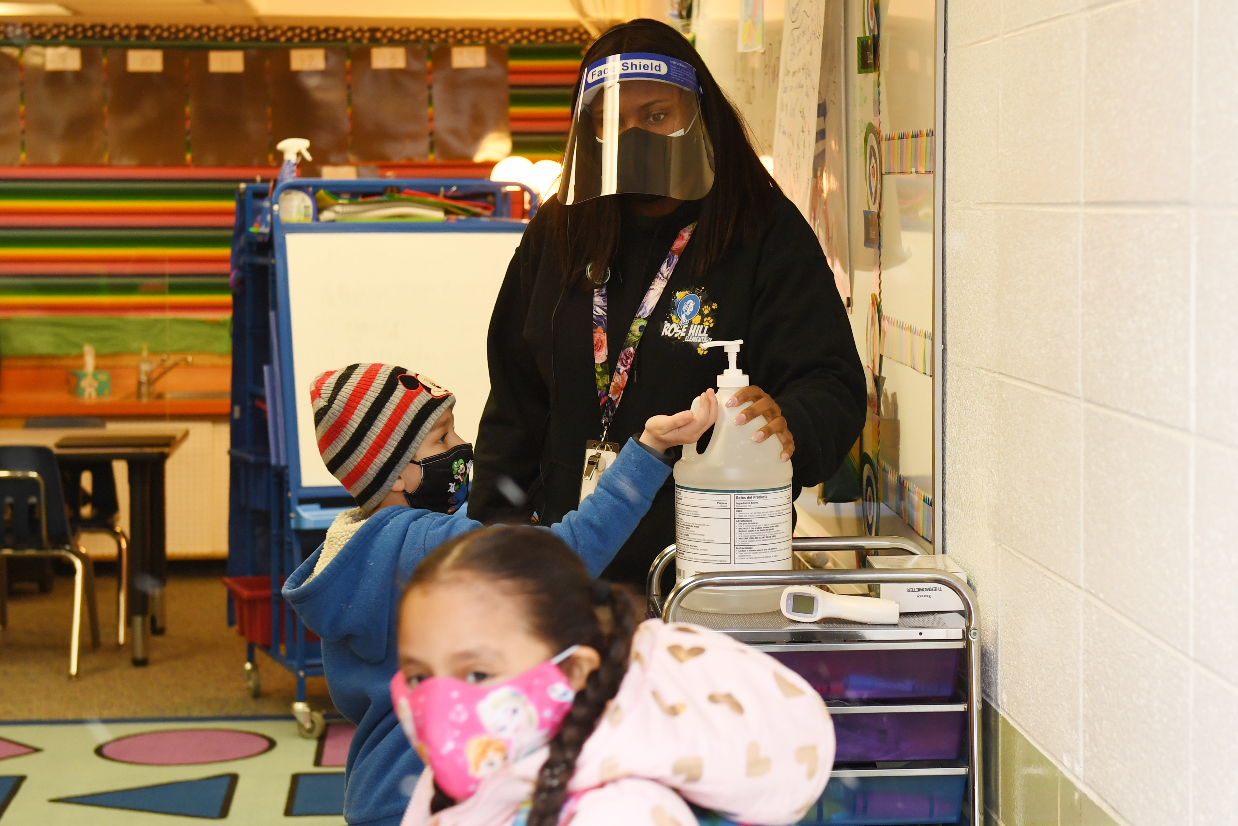 A teacher wearing a mask and face shield helps masked students use hand sanitizer before starting class in an elementary classroom.