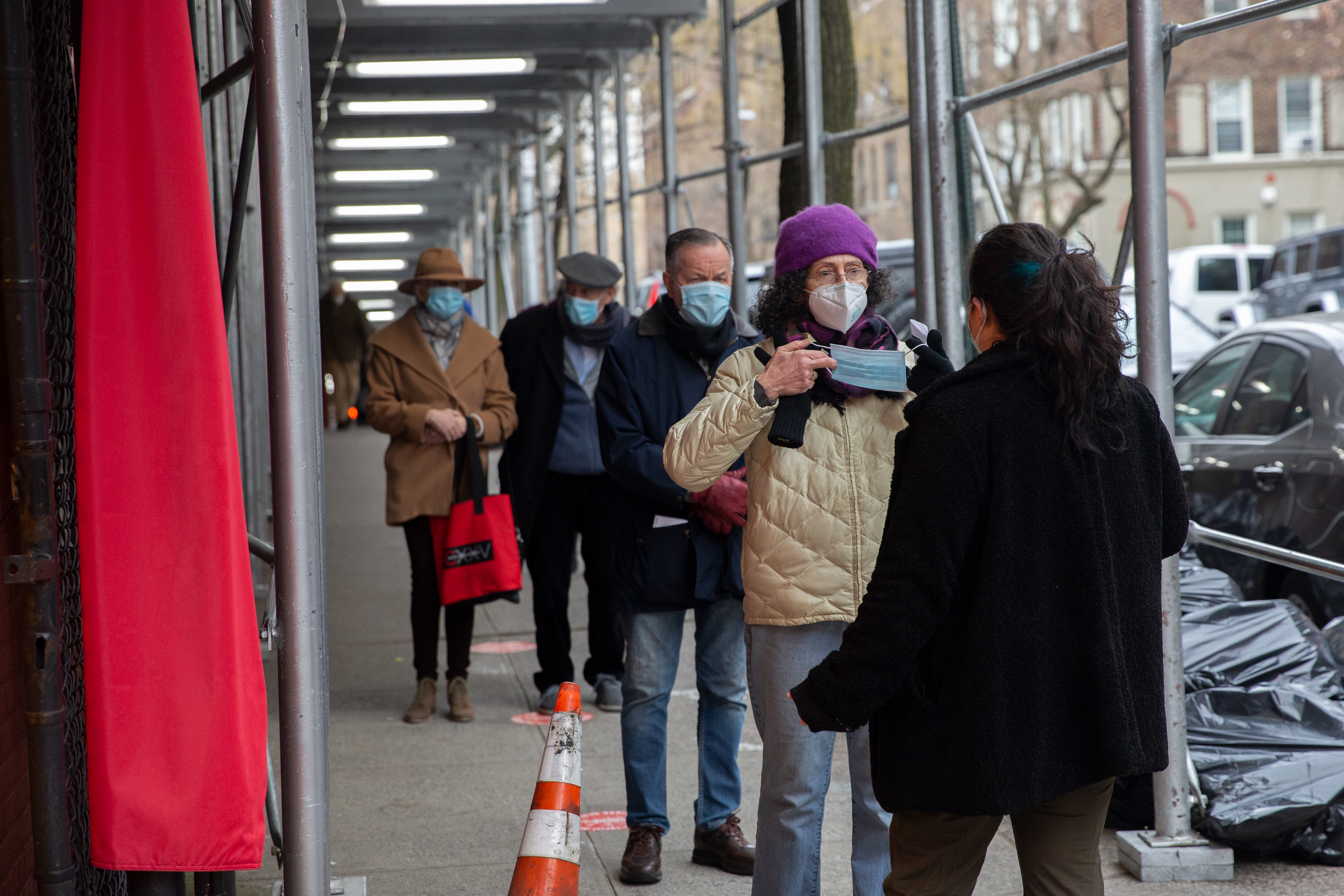 A health care worker speaks with people waiting to get their coronavirus vaccine shot at the Washington Heights Armory, Jan. 26, 2021.