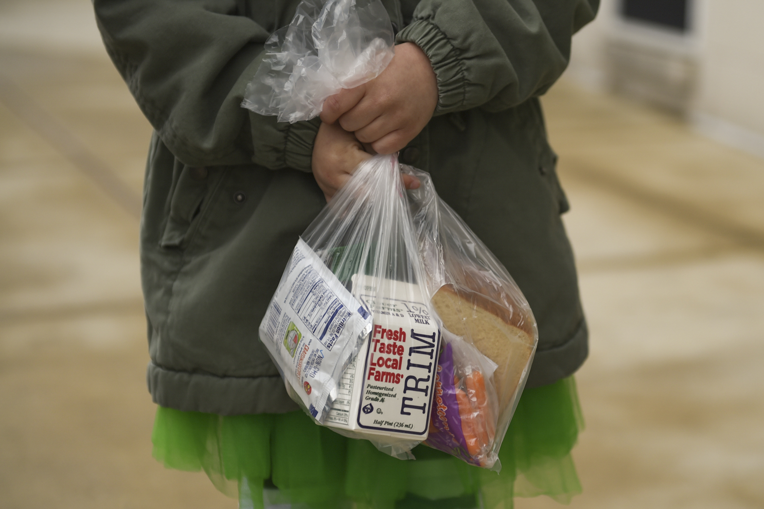 Child holds a plastic bag containing a carton of milk and other breakfast foods.