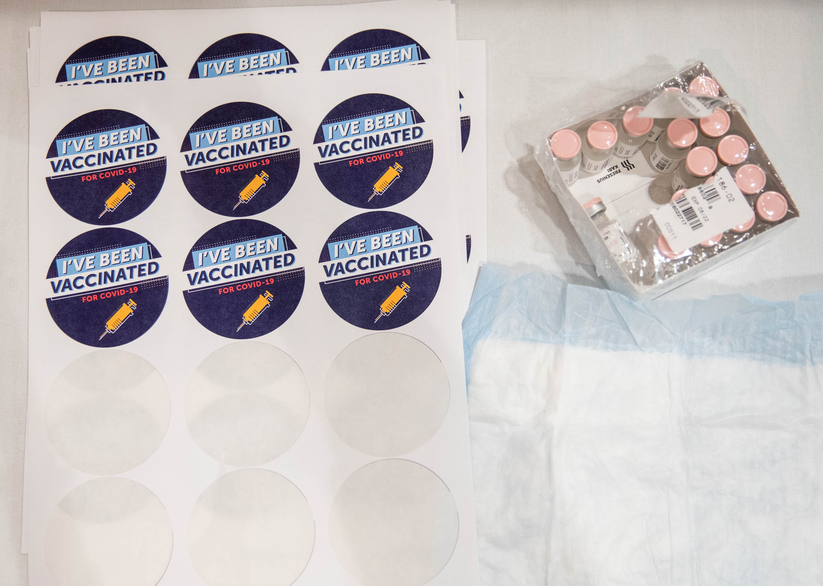 """A box of vials filled with Pfizer's Covid-19 vaccine five doses per vial sits next to a pile of stickers that read """"I've been vaccinated for Covid-19"""" on the preparation table at Thomas Jefferson University Hospital in Philadelphia, Pennsylvania, on December 16, 2020."""