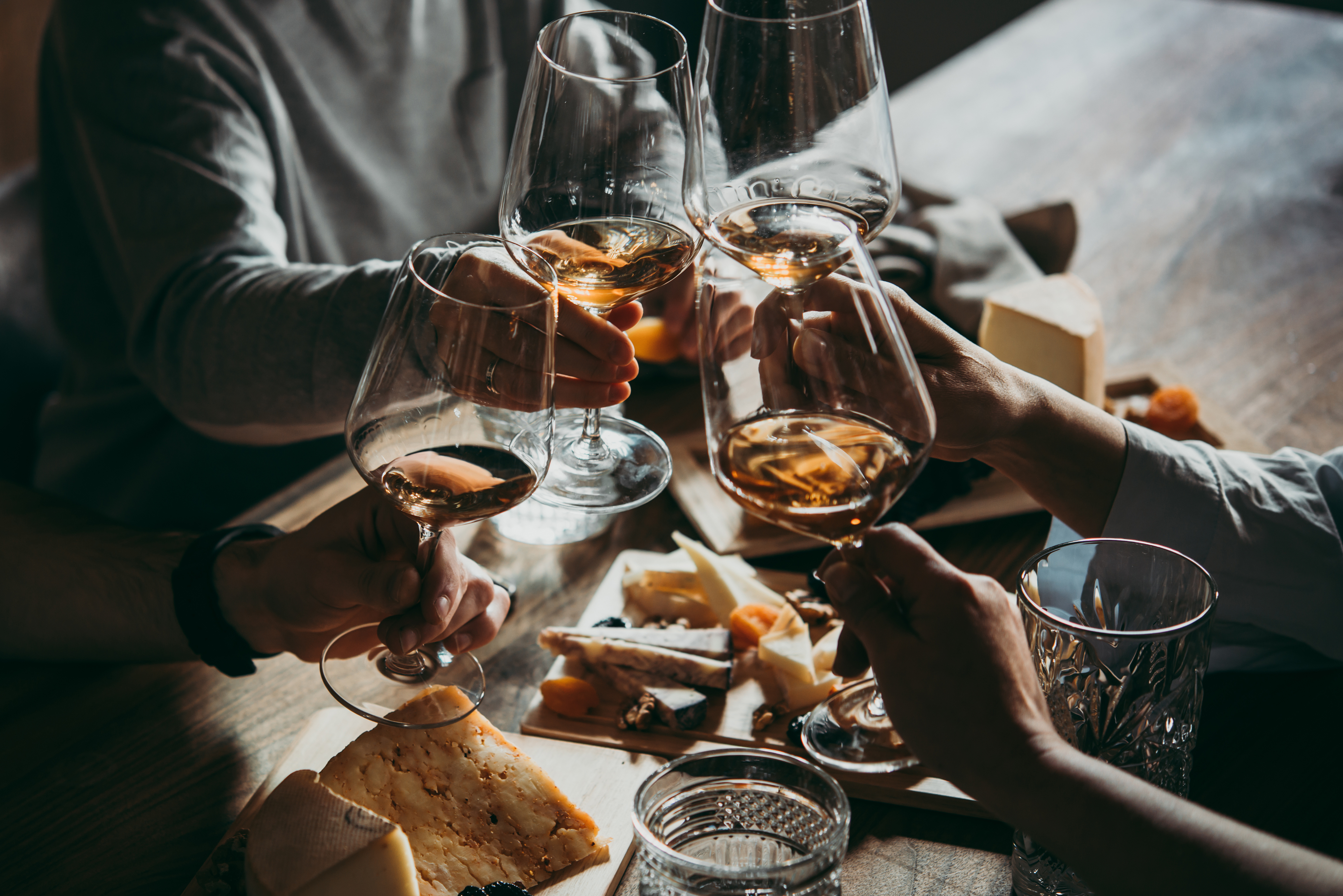 Hands clink glasses of wine together over a spread of meats and cheese.