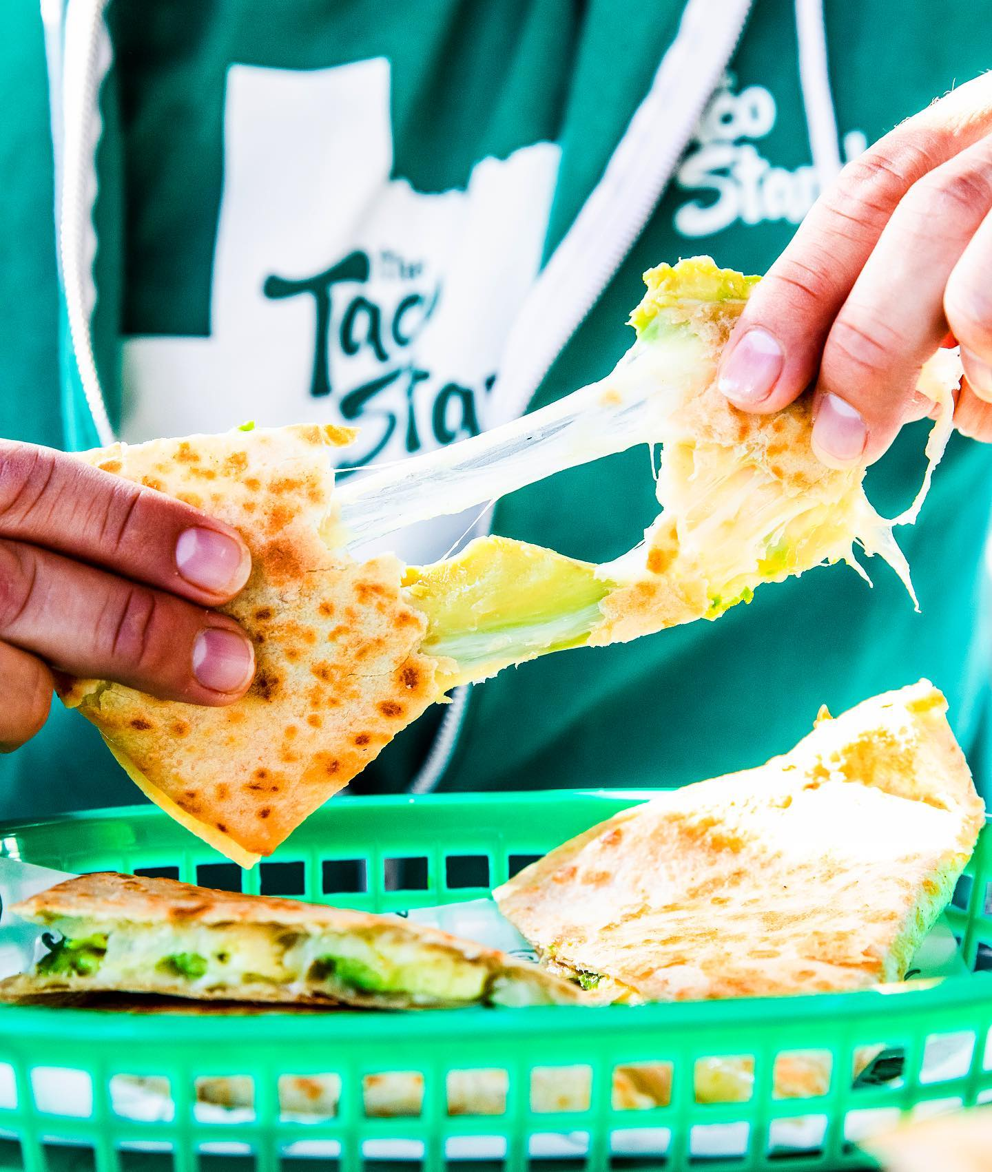 two hands pulling apart a cheesy quesadilla