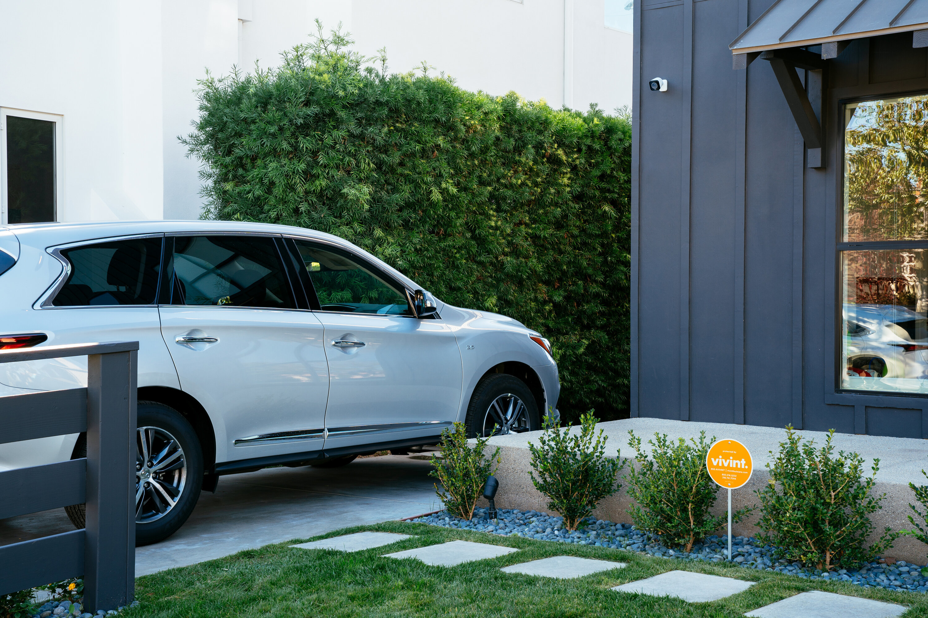 Edge of a home with a security camera, a Vivint sign in the front yard, and a car parked in the driveway