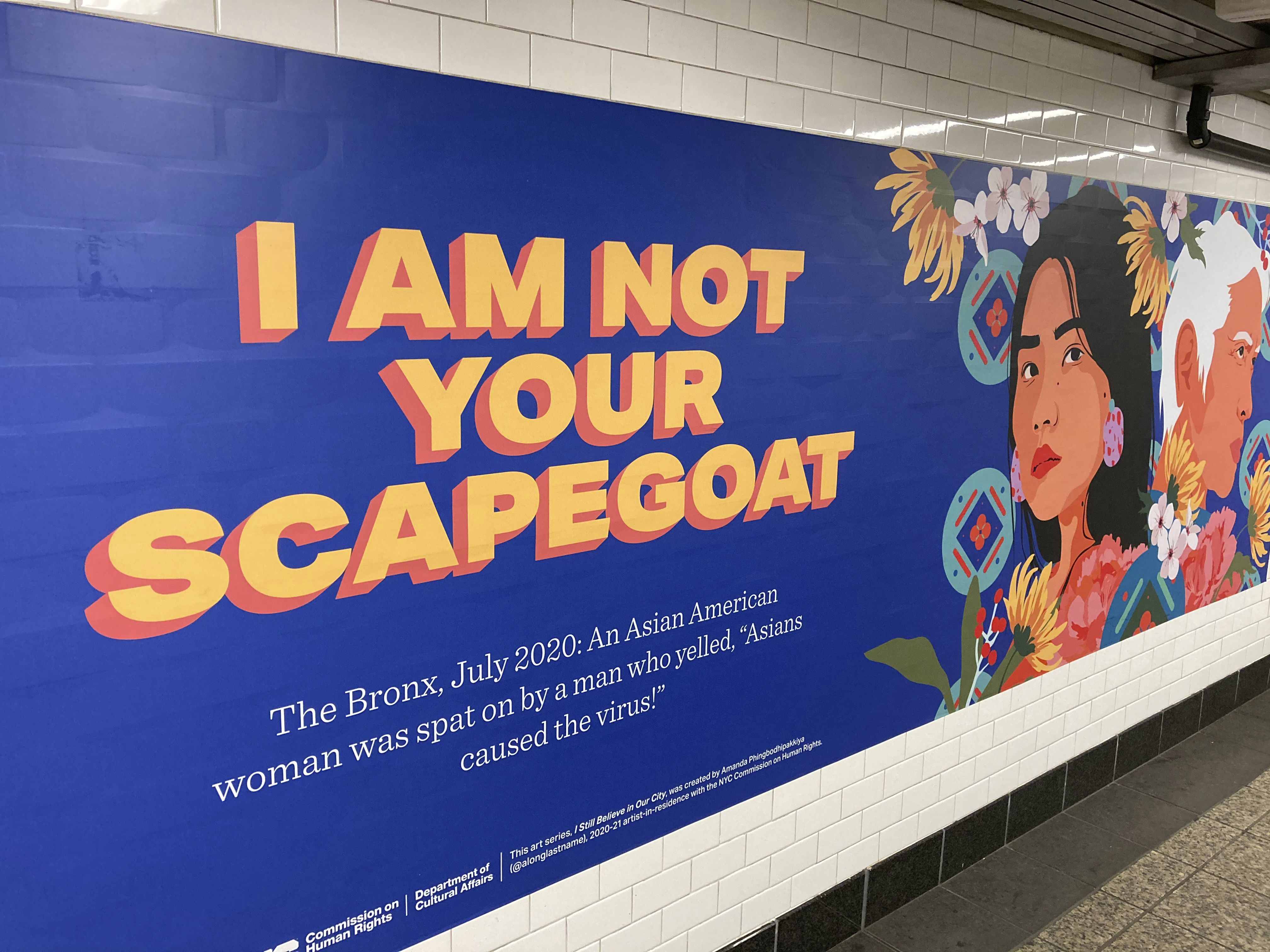 "A billboard in a subway in Brooklyn reads, ""I am not your scapegoat"" and features an illustration of an Asian woman."